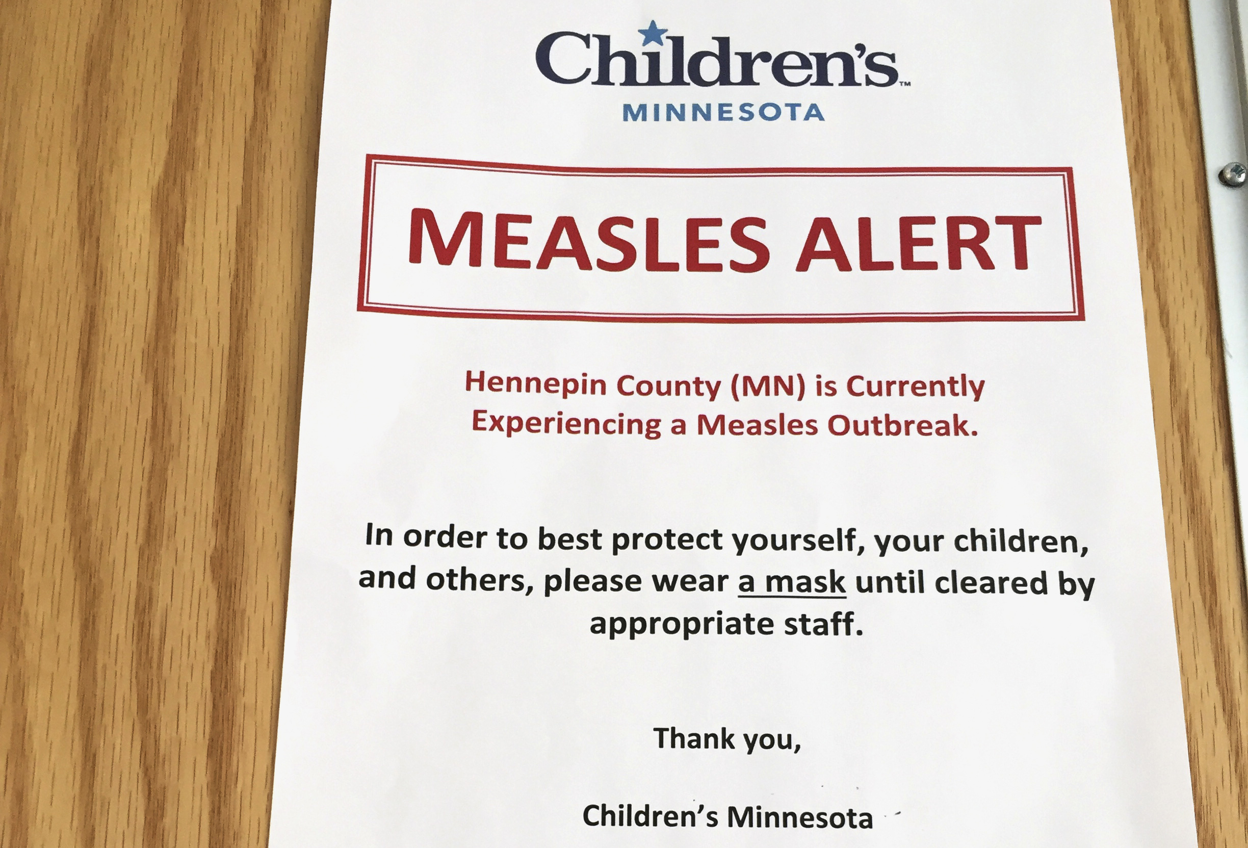 In this May 2, 2017 photo, a sign at the specialty clinic at Children's Minnesota in Minneapolis, alerts patients to a measles outbreak in the area.