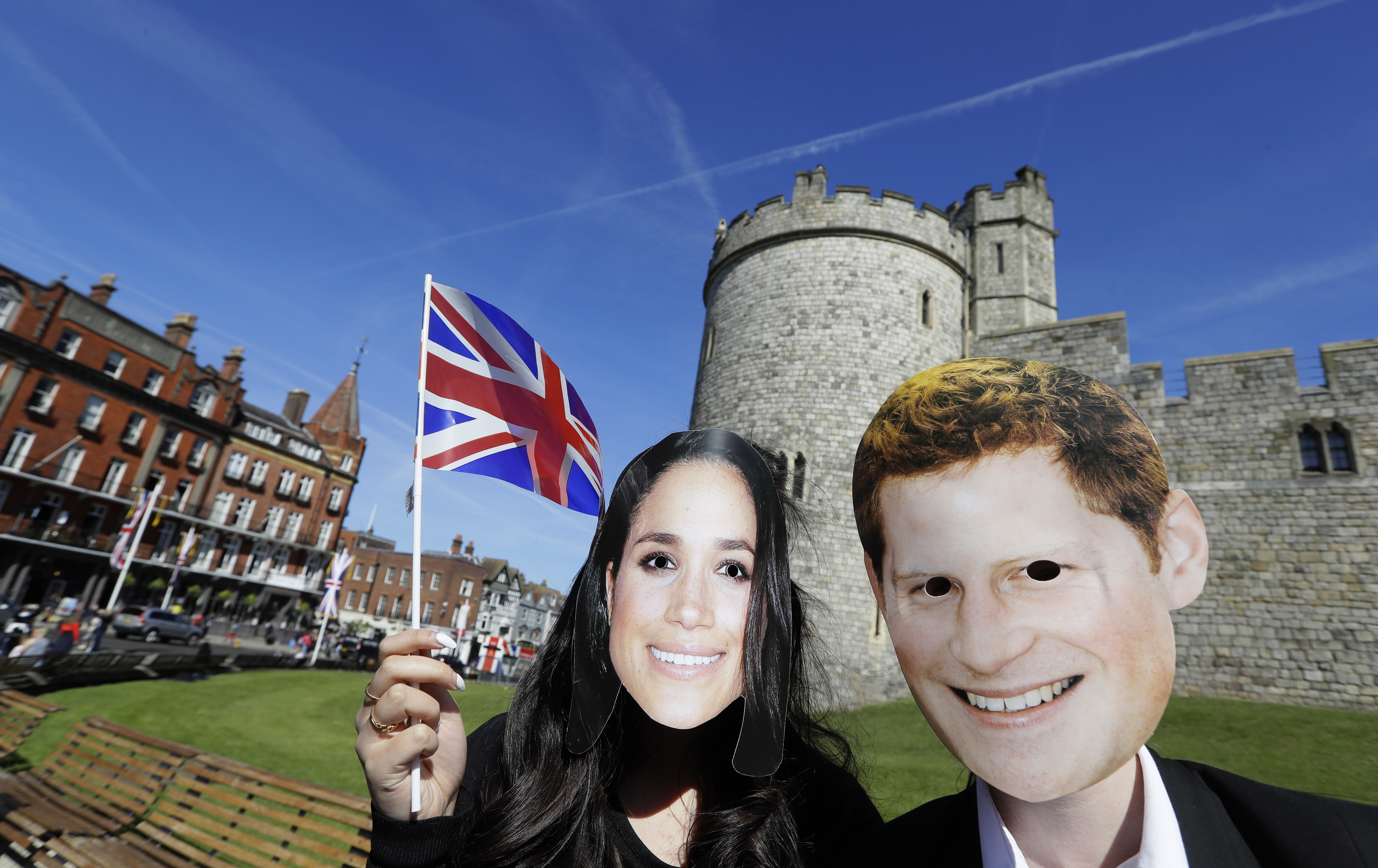 People wearing face masks of Britain's Prince Harry and Meghan Markle pose for a photograph outside Windsor Castle in Windsor, England, May 14, 2018.