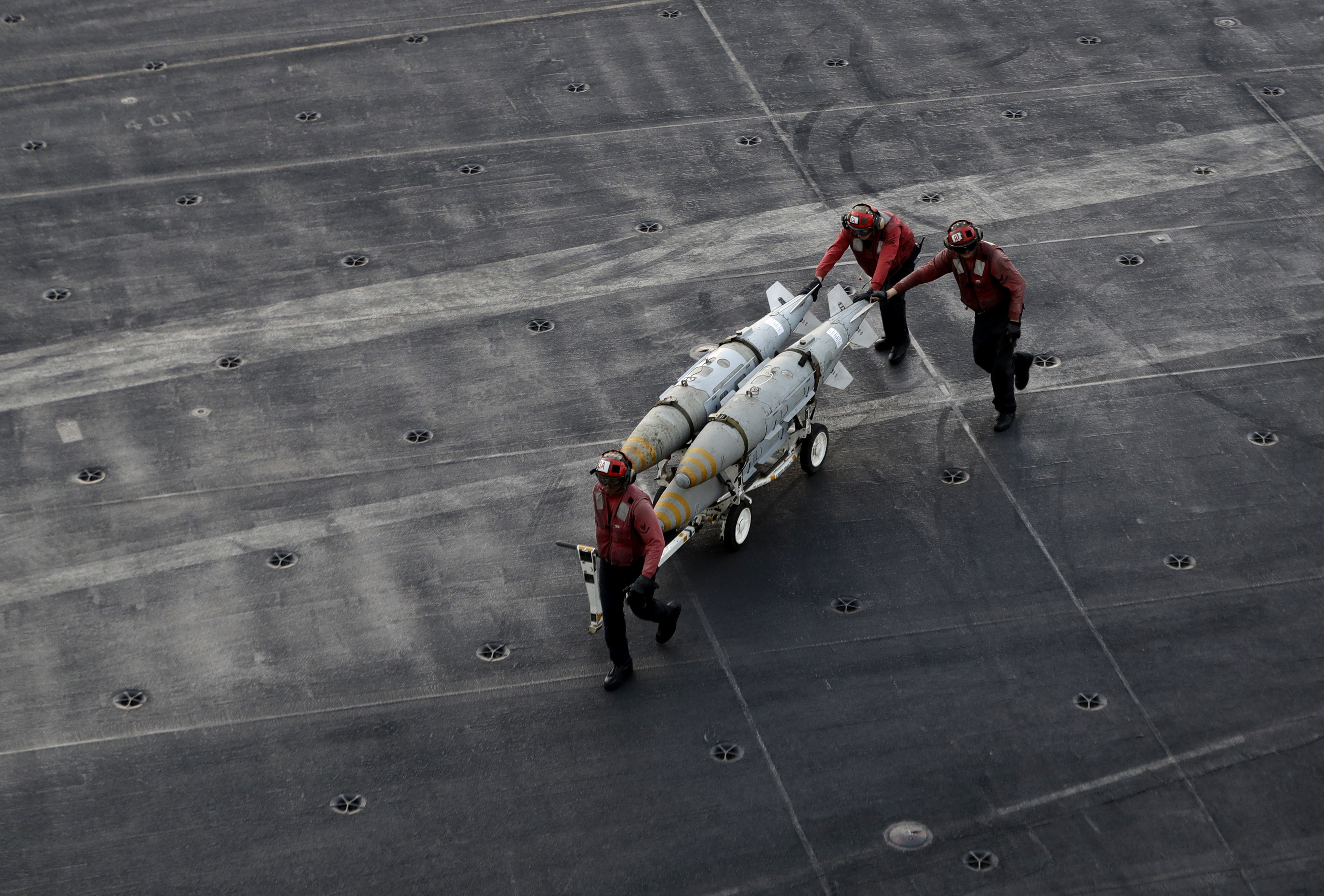FILE - U.S. Navy sailors push ammunition across the deck of the U.S.S. Dwight D. Eisenhower aircraft carrier, Nov. 21, 2016, as the ship carries out military operations against IS extremists in Syria and Iraq.
