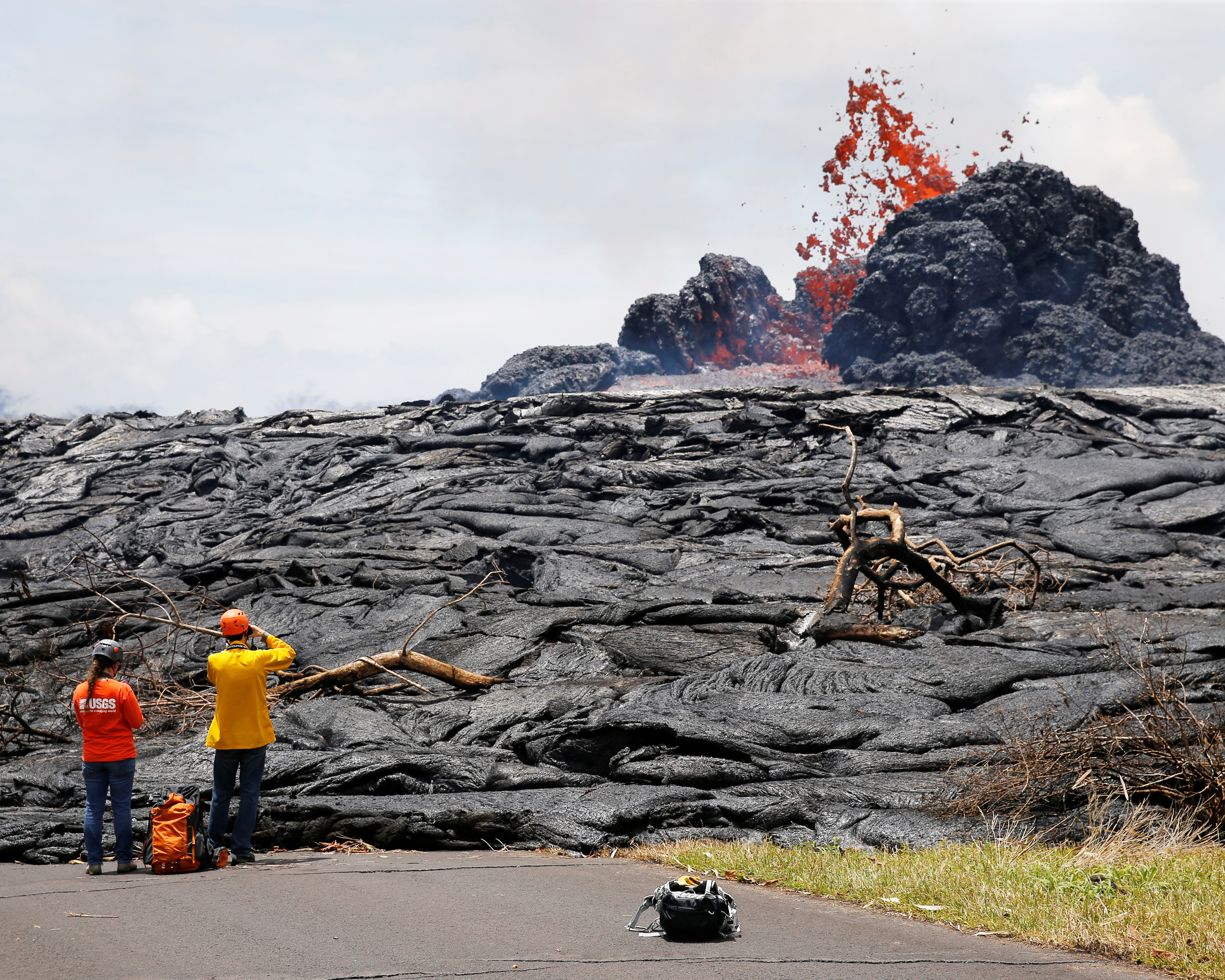 Sarah Conway, left, and Matt Patrick, both from USGS Hawaiian Volcano, watch lava erupting from a fissure in the Leilani Estates near Pahoa, Hawaii, May 24, 2018.