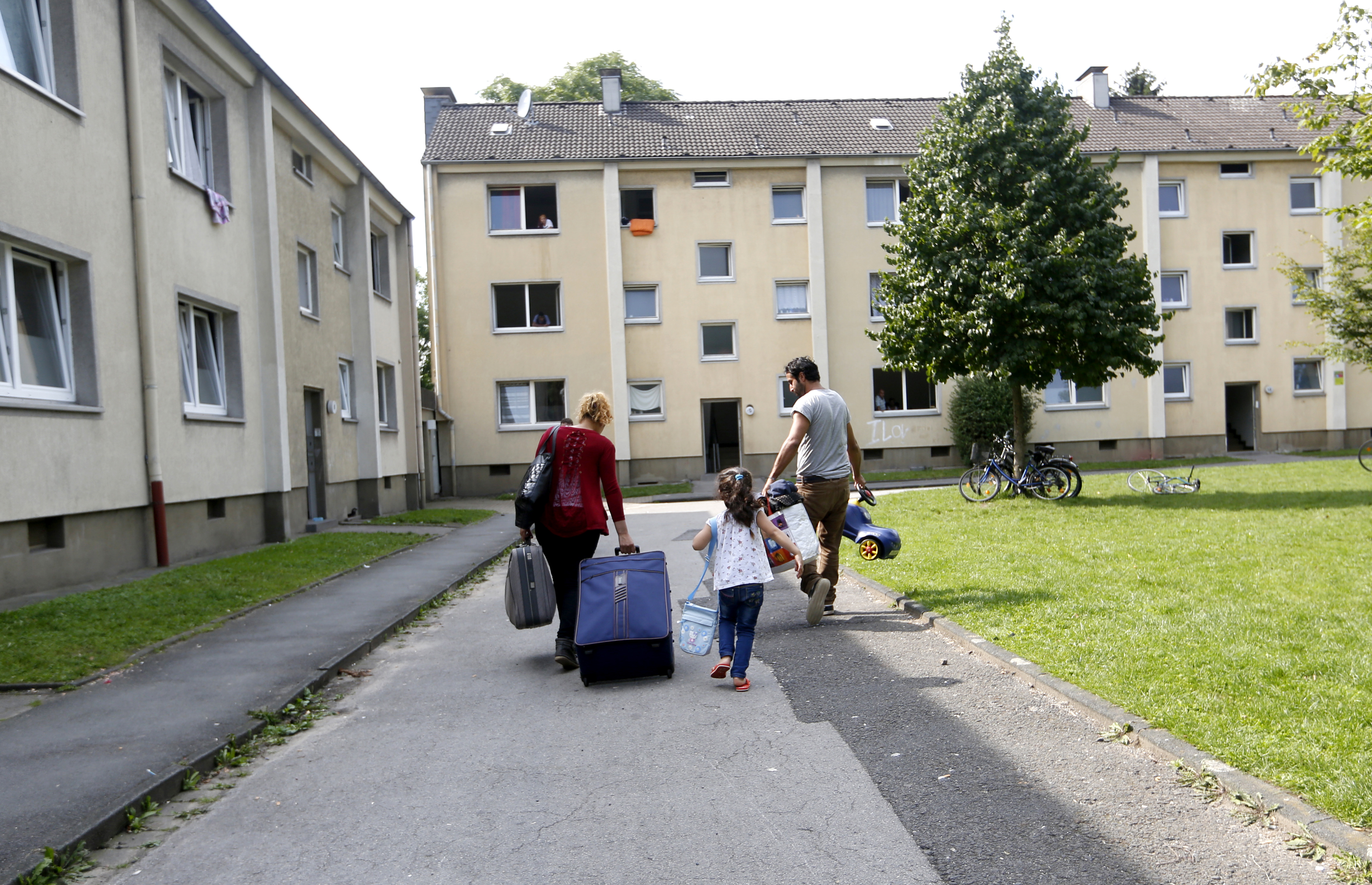 4-year-old-refugee Lilas from Syria and her parents walk to their refugee home in Muelheim an der Ruhr, Germany, after receiving articles for daily use prepared by donors at a distribution center, Aug, 20, 2015.