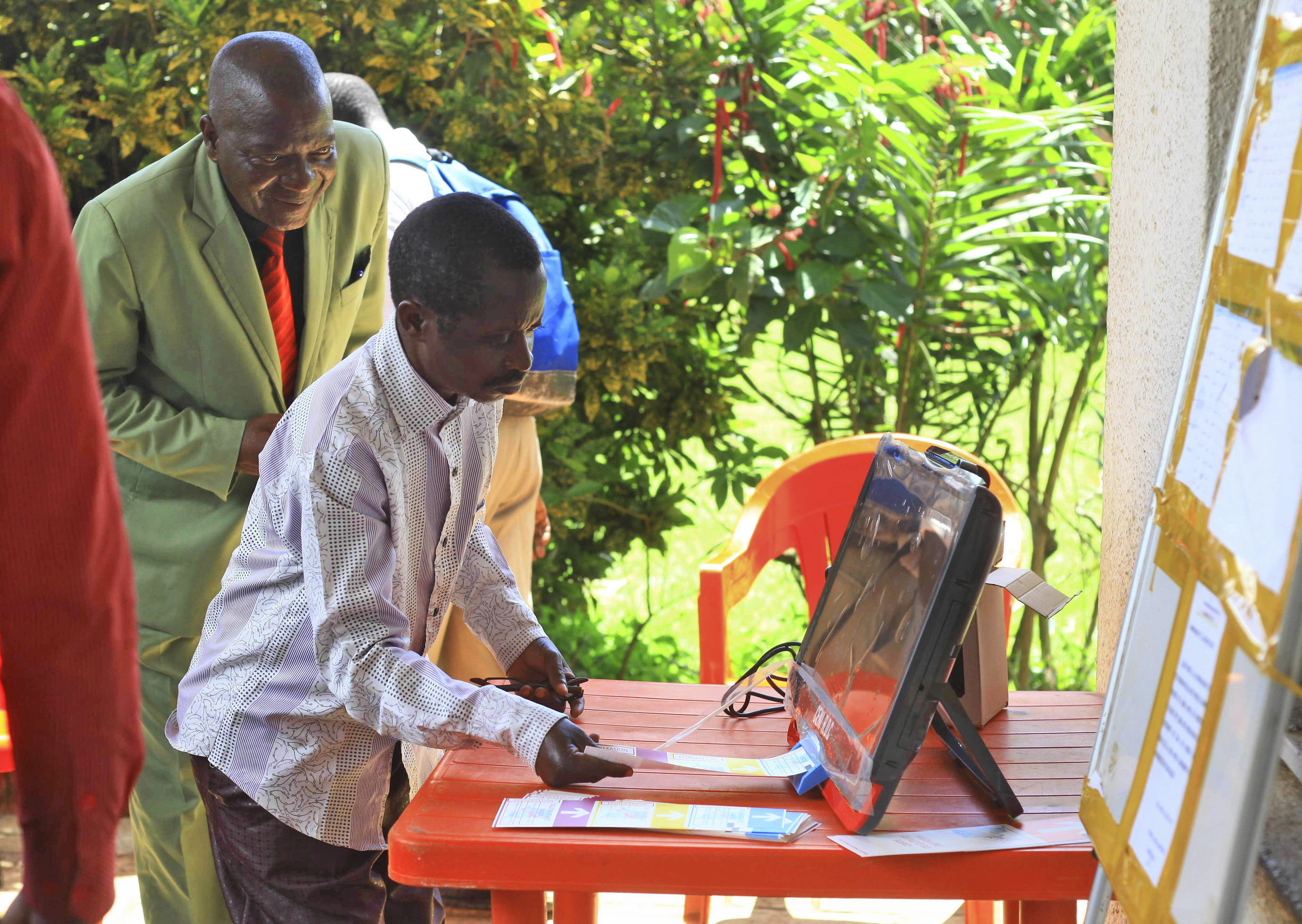 In this photo taken Oct. 16, 2018, a man demonstrates using an electronic voting machine that will be used later in the year for the next election in Beni, Eastern Congo.
