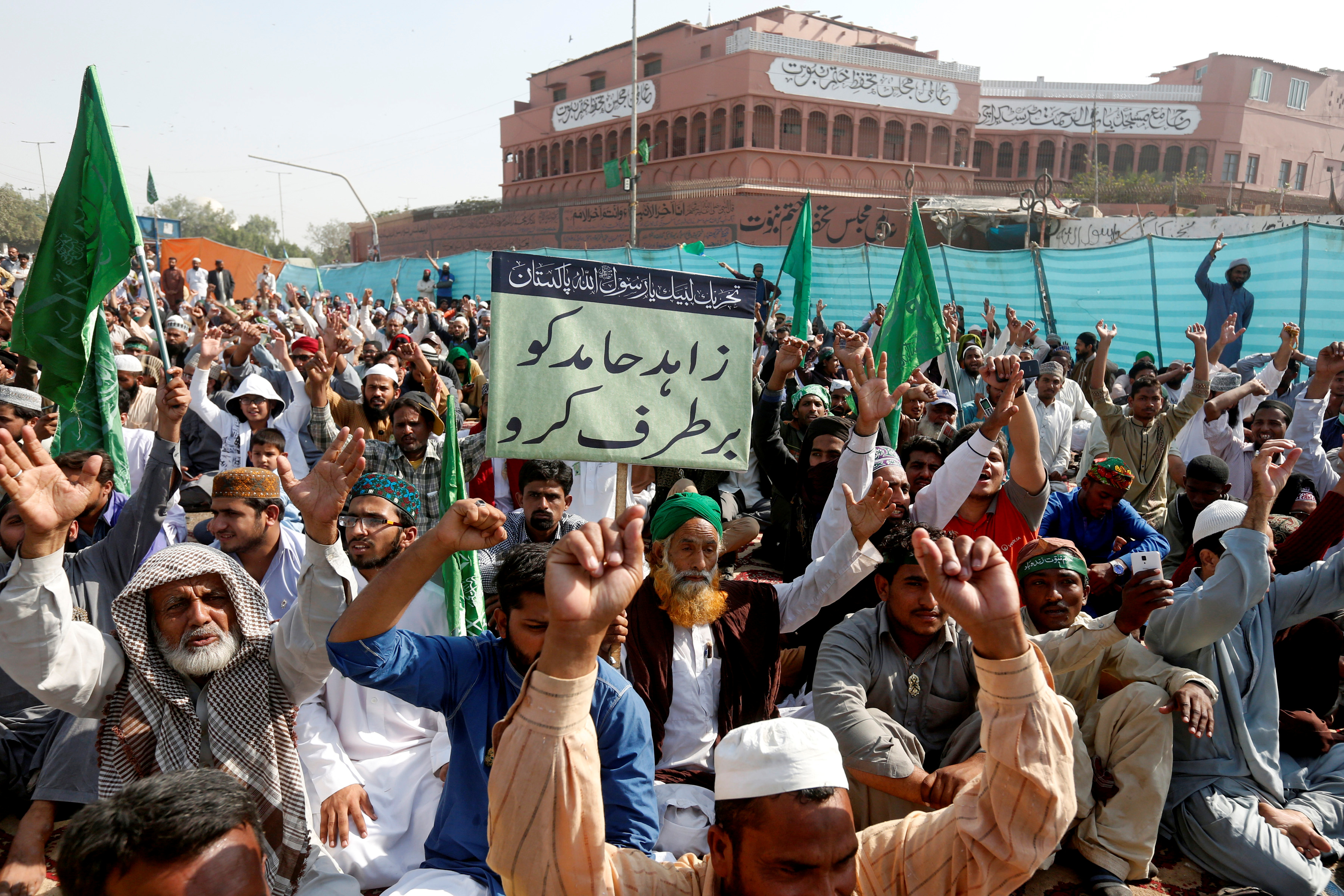 """A supporter of the Tehreek-e-Labaik Pakistan, an Islamist political party, holds a sign, which reads in Urdu, """"remove Zahid Hamid"""" during a sit-in protest along a main road in Karachi, Nov. 27, 2017."""