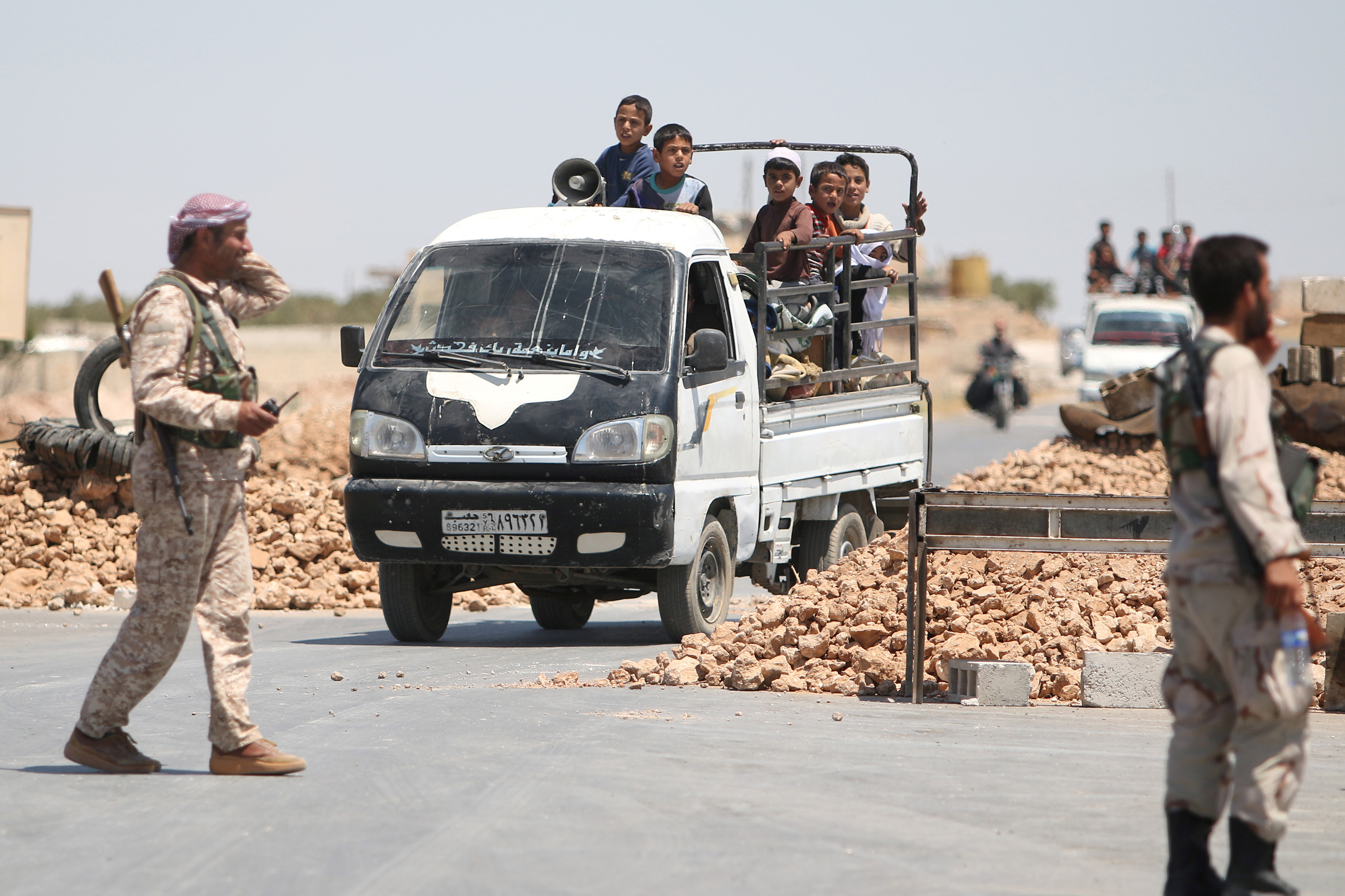 Syria Democratic Forces (SDF) fighters man a checkpoint as civilians on pick-up trucks evacuate from the southern districts of Manbij city after the SDF advanced into it in Aleppo Governorate, Syria, July 1, 2016.