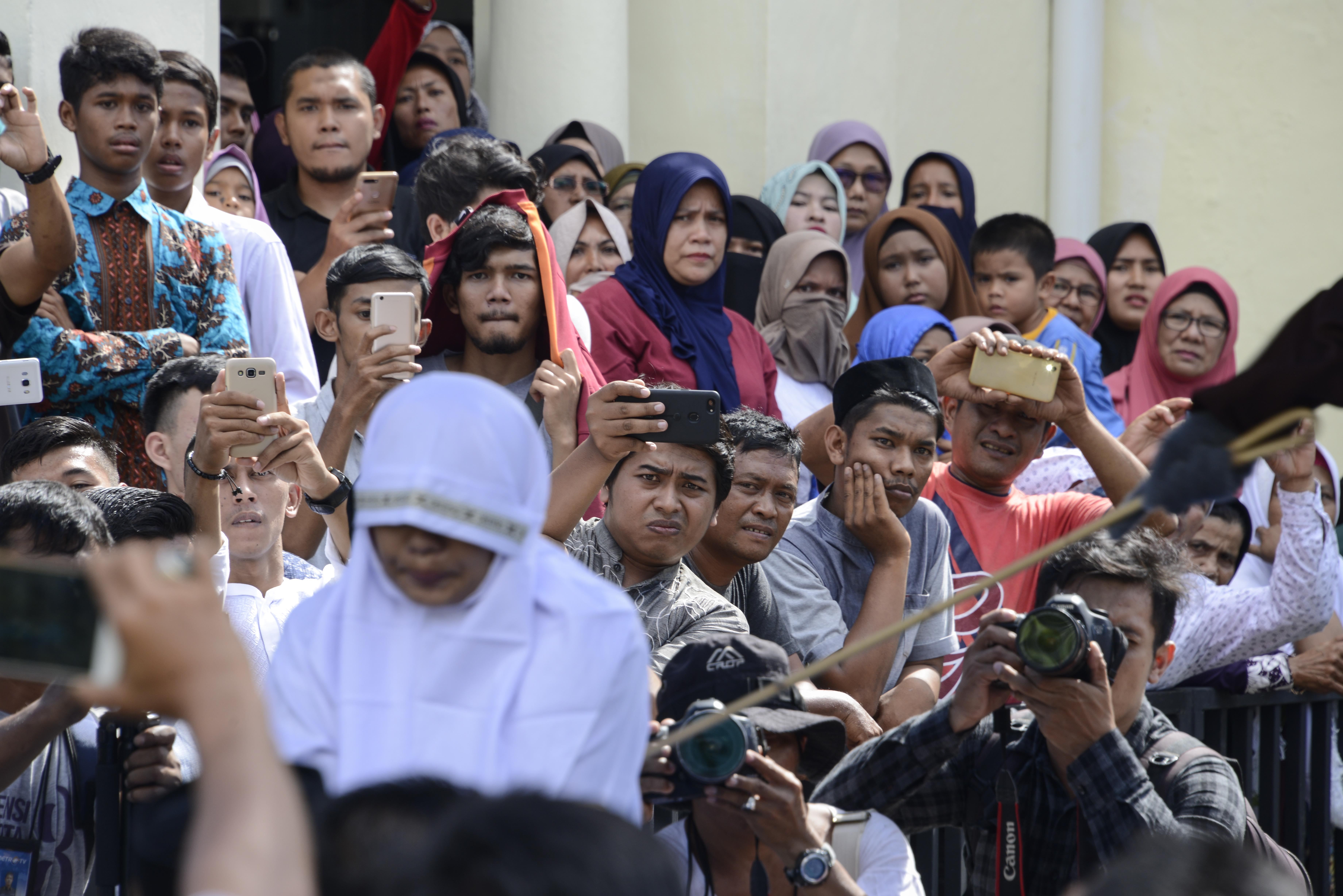 Onlookers watch as a member of Indonesia's Sharia police, at right outside the frame, whips a non-Muslim woman, bottom left, for trading alcohol during a public caning ceremony outside a mosque in Banda Aceh, the capital of Aceh province, July 13, 20...