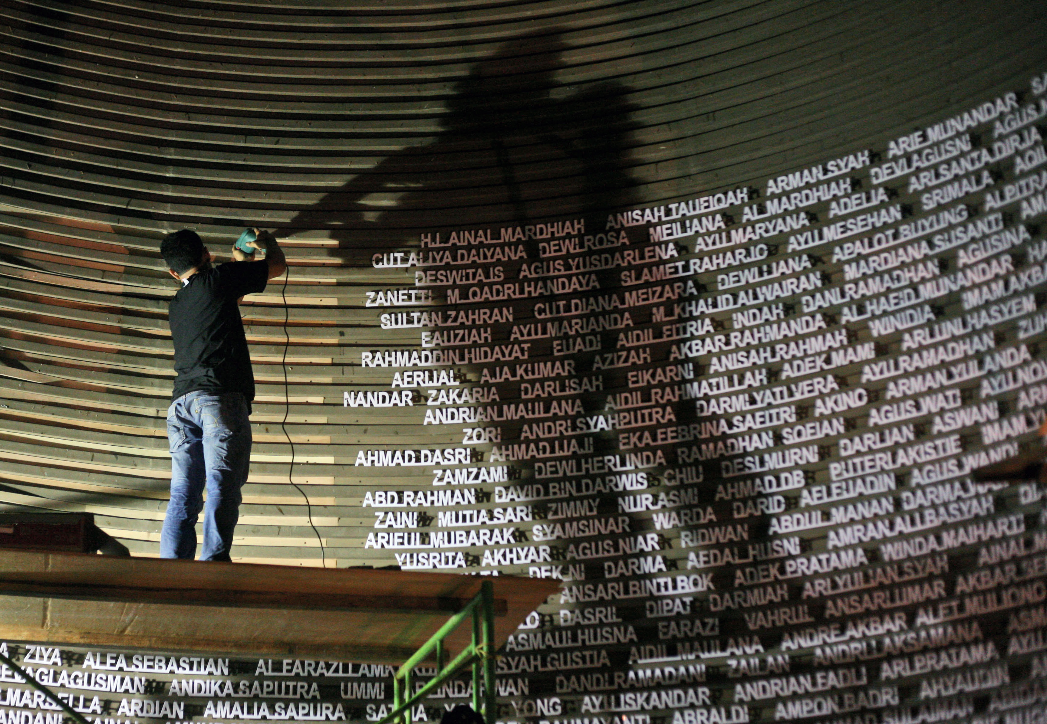 A worker installs the names of the victims of the 2004 Indian Ocean tsunami on the wall of the Tsunami Museum ahead of the 10th anniversary of the killer waves in Banda Aceh, Aceh province, Indonesia, Thursday, Dec. 4, 2014.