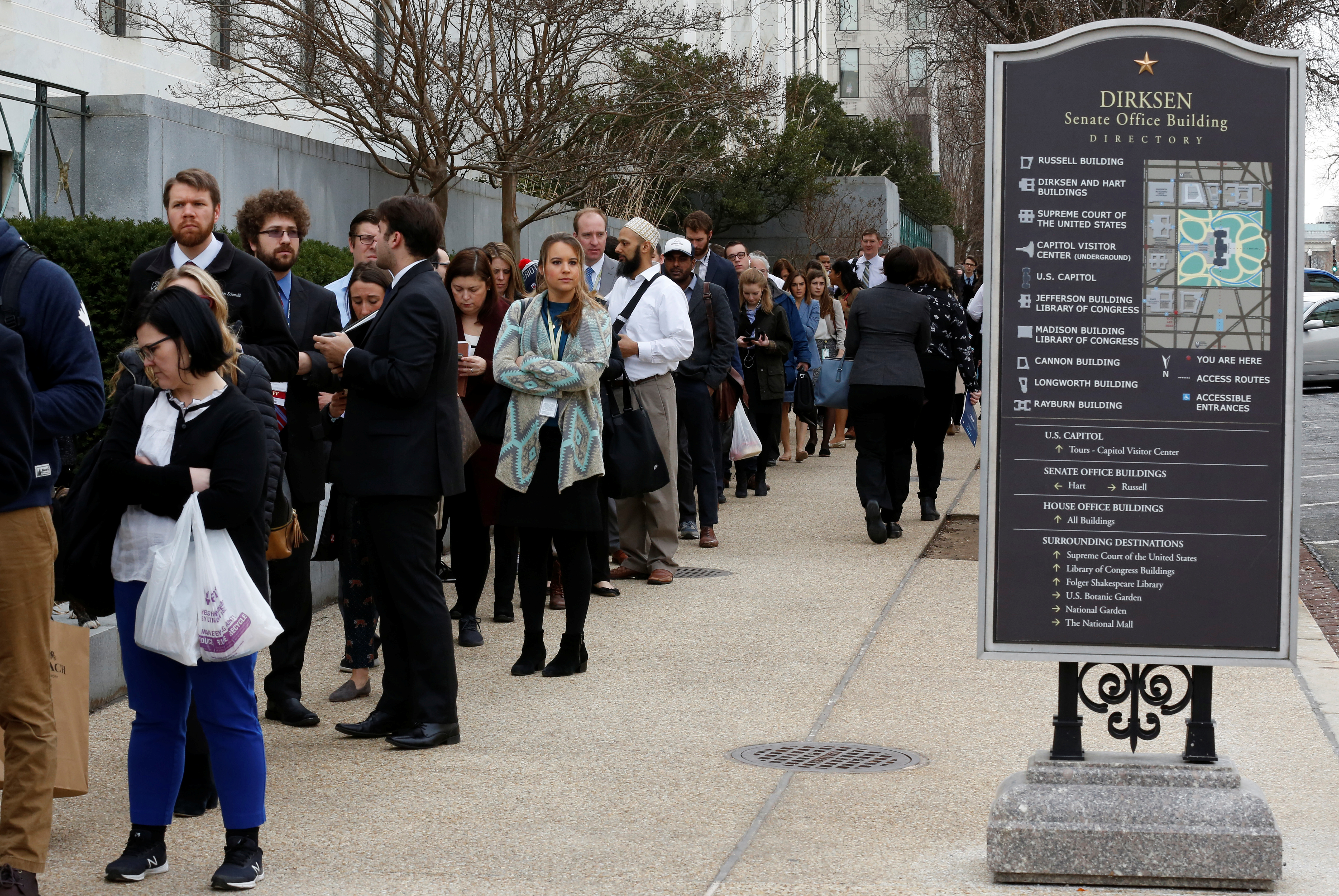 Congressional staffers wait in an excessively long line to enter the Dirksen Senate office building during the third day of a shut down of the federal government in Washington, Jan. 22, 2018.
