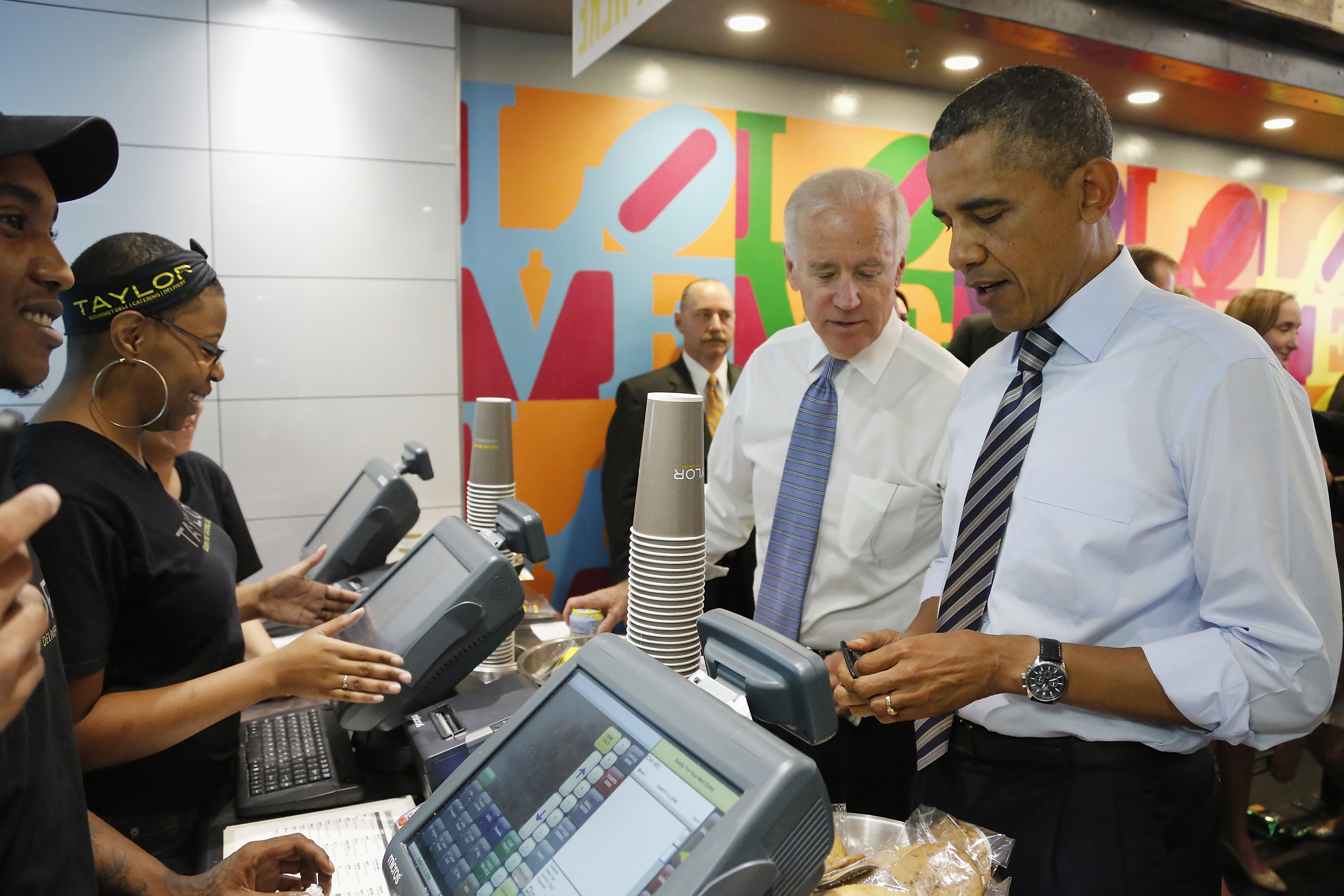 U.S. President Barack Obama (R) opens his wallet to buy lunch for himself and Vice President Joe Biden (2nd R) at a sandwich shop near the White House in Washington, October 4, 2013. House Republicans held their ground on Friday in a standoff with Ob...