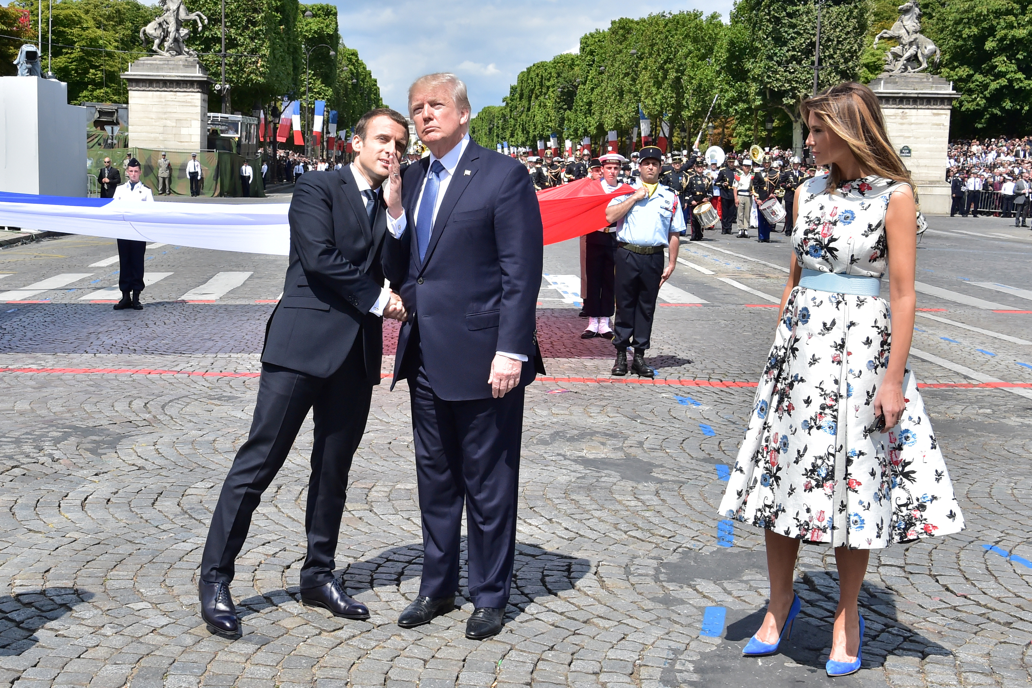 FILE - French President Emmanuel Macron, left, shakes hands with U.S. President Donald Trump, next to U.S. first lady Melania Trump during the traditional Bastille Day military parade on the Champs-Elysees in Paris, July 14, 2017.