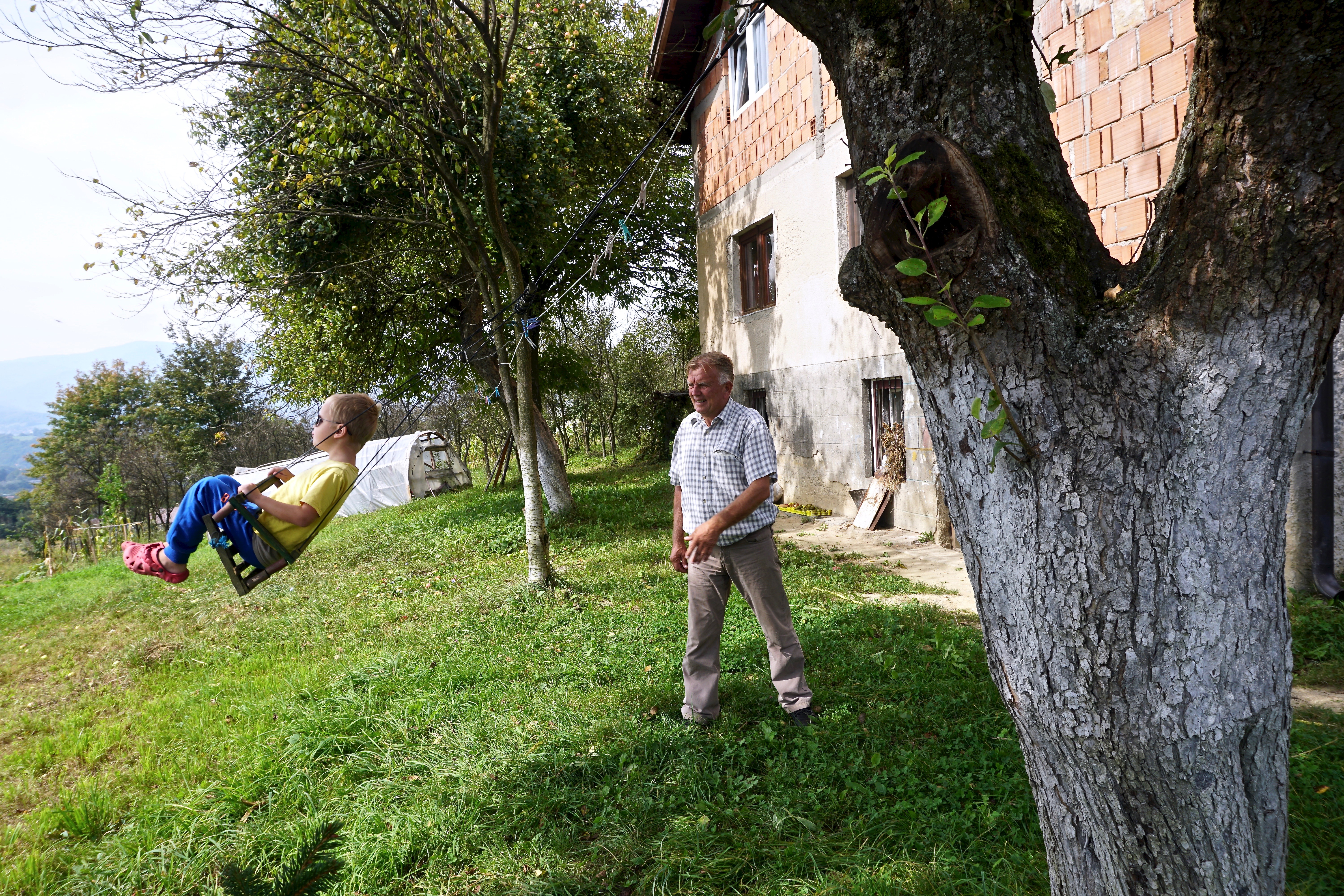 Huso Ahmići: Huso Ahmići, aged 72, plays with his grandson in the garden of the family home that was razed during a Croatian 'ethnic cleansing' assault on the villages of the Lašva Valley in 1993. His parents died when the house was razed. H...