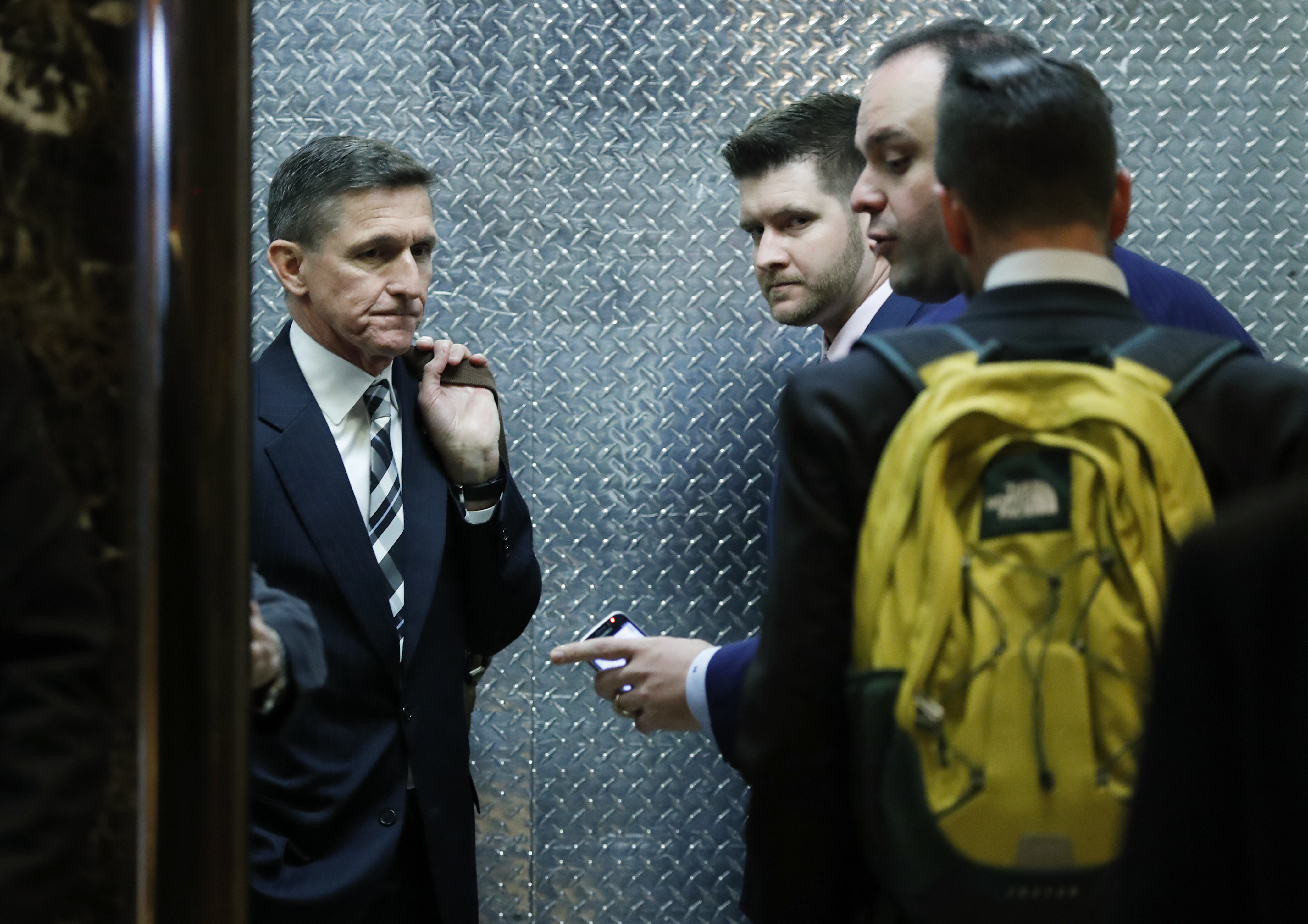 FILE -  retired Lt. Gen Michael Flynn, left, his son Michael G. Flynn, second from left, and Boris Epshteyn, a spokesman for President-elect Donald Trump, third from left, board an elevator at Trump Tower in New York.