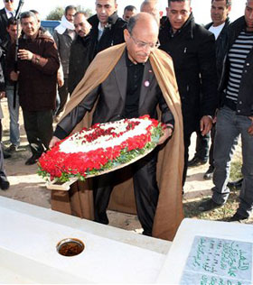 Tunisian President, Moncef Marzouki places flowers at the tombstone of Mohamed Bouazizi, a 26-year-old who set himself alight on Dec. 17, 2010
