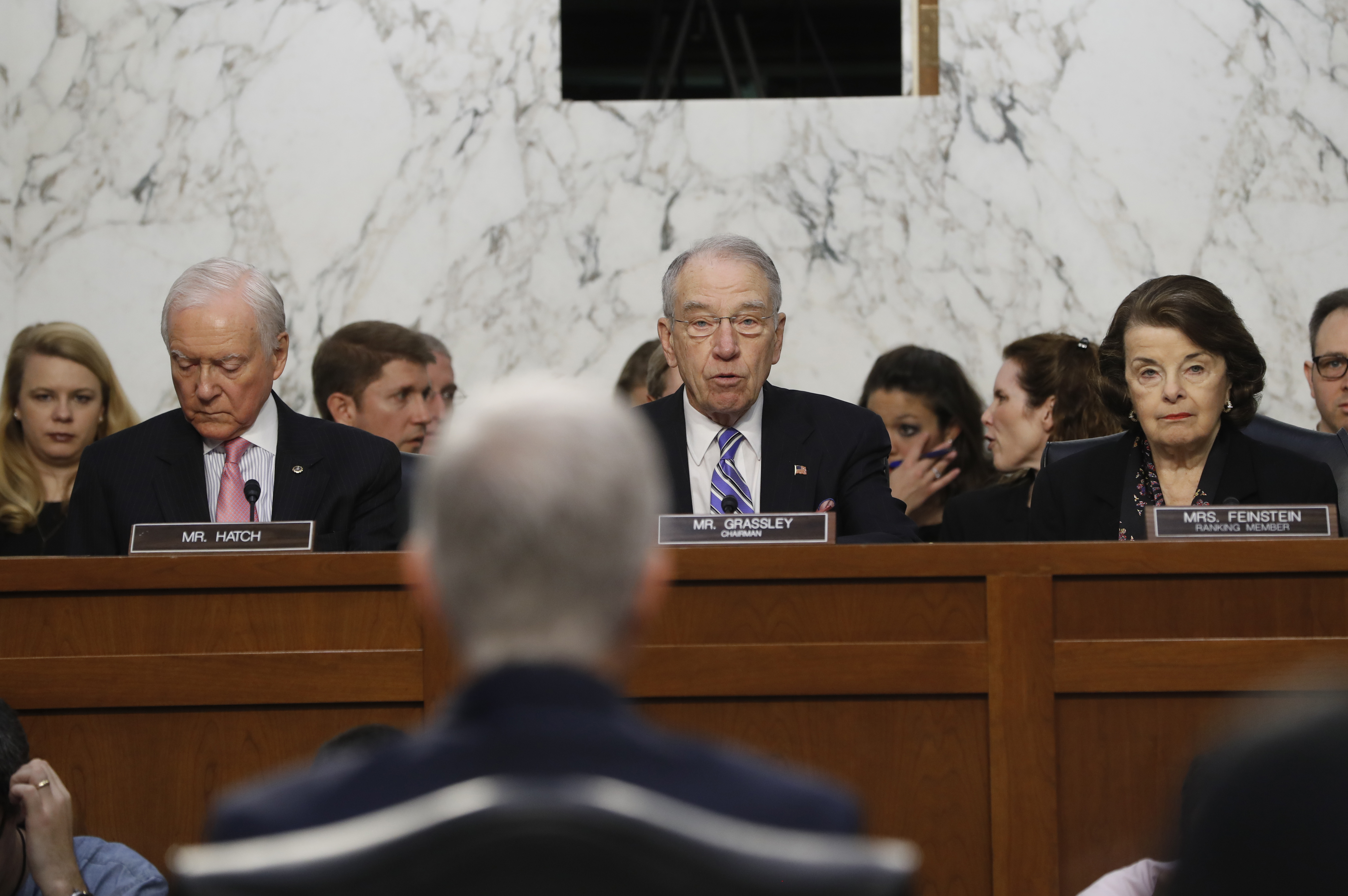 Supreme Court Justice nominee Neil Gorsuch, back to camera, listens on Capitol Hill in Washington, March 21, 2017, as Senate Judiciary Committee Chairman Sen. Charles Grassley, R-Iowa, flanked by the committee ranking member Sen. Dianne Feinstein, D-...