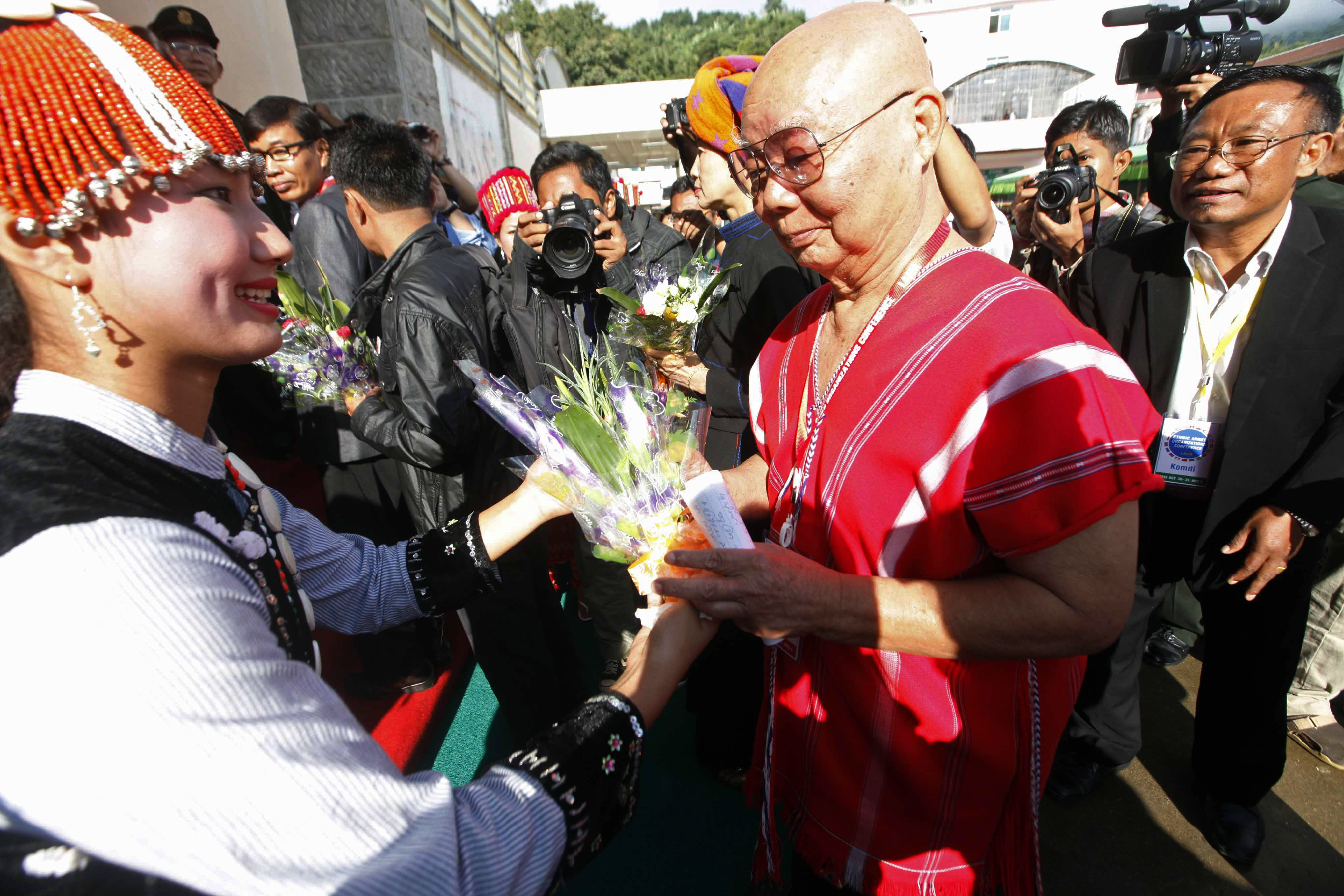 General Mutu Say Poe, second from right, Chairman of Karen National Union (KNU), receives flowers from a woman upon his arrival to attend ethnic armed organizations conference in Laiza, Burma, Oct. 30, 2013.