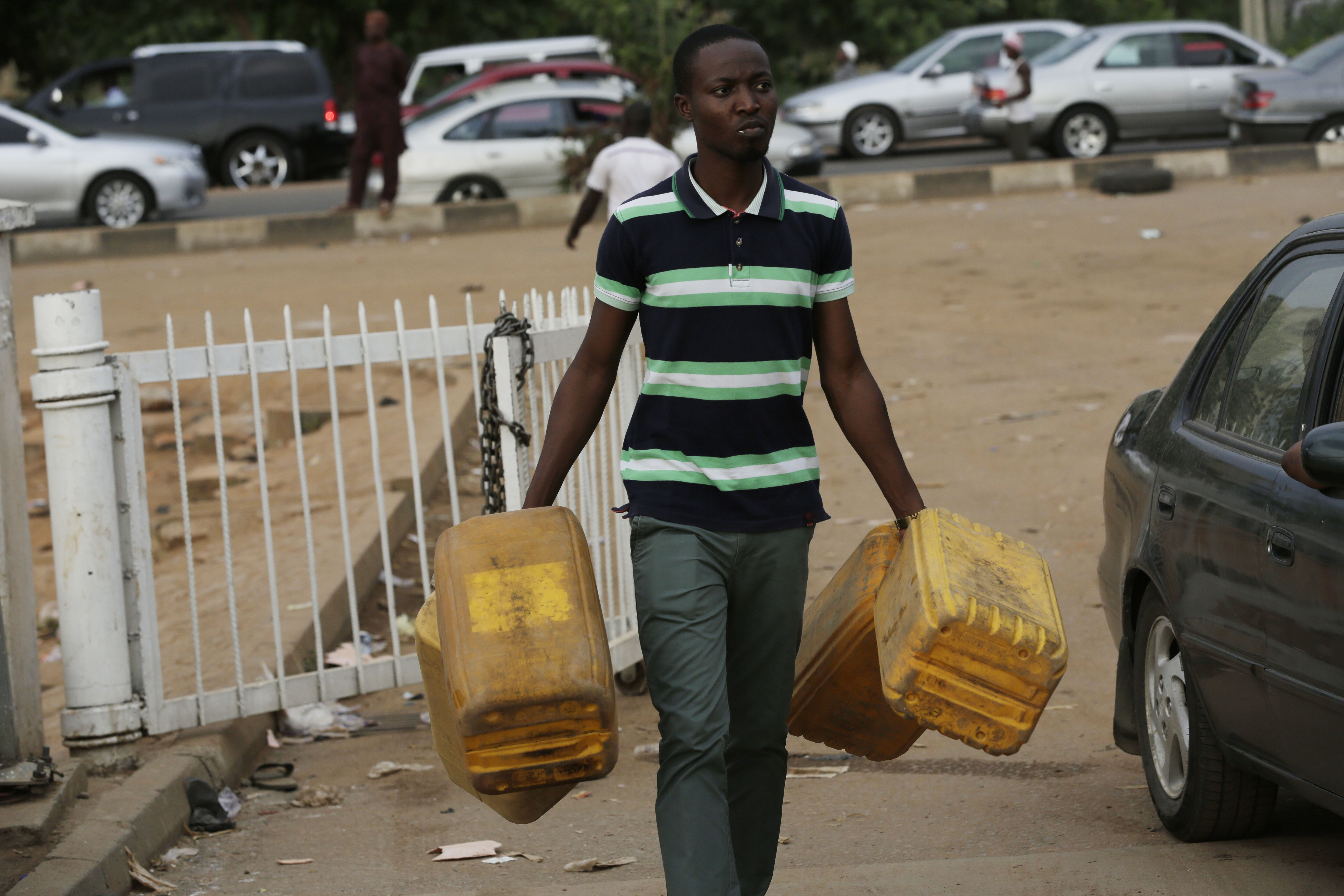 A man carries empty containers to buy fuel at a petrol station in Abuja, Nigeria, May 26, 2015.