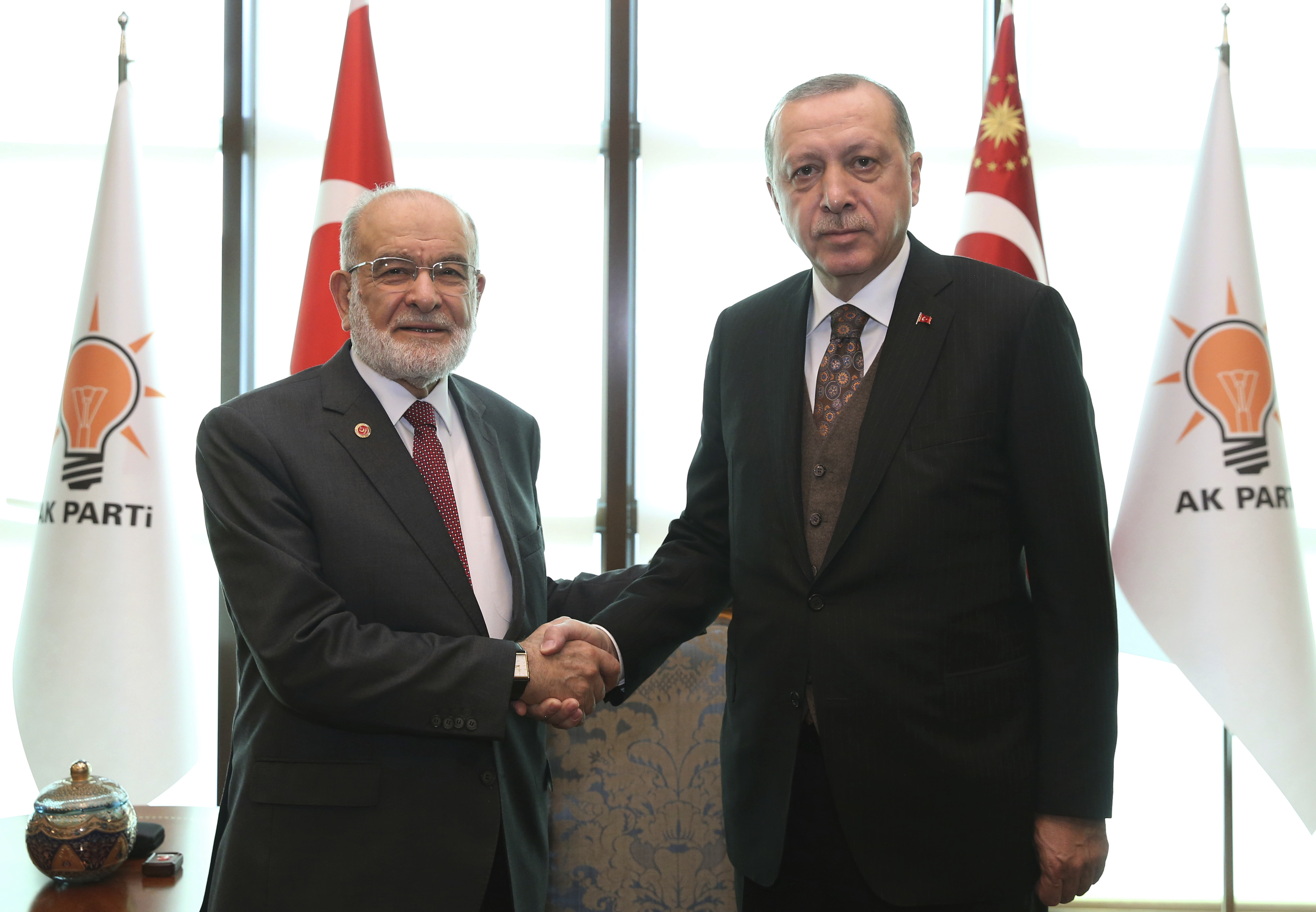 FILE - Turkey's President Recep Tayyip Erdogan, right, shakes hands with Temel Karamollaoglu, the leader of pro-Islamic Felicity Party, before their talks in Ankara, Turkey, Feb. 9, 2018.