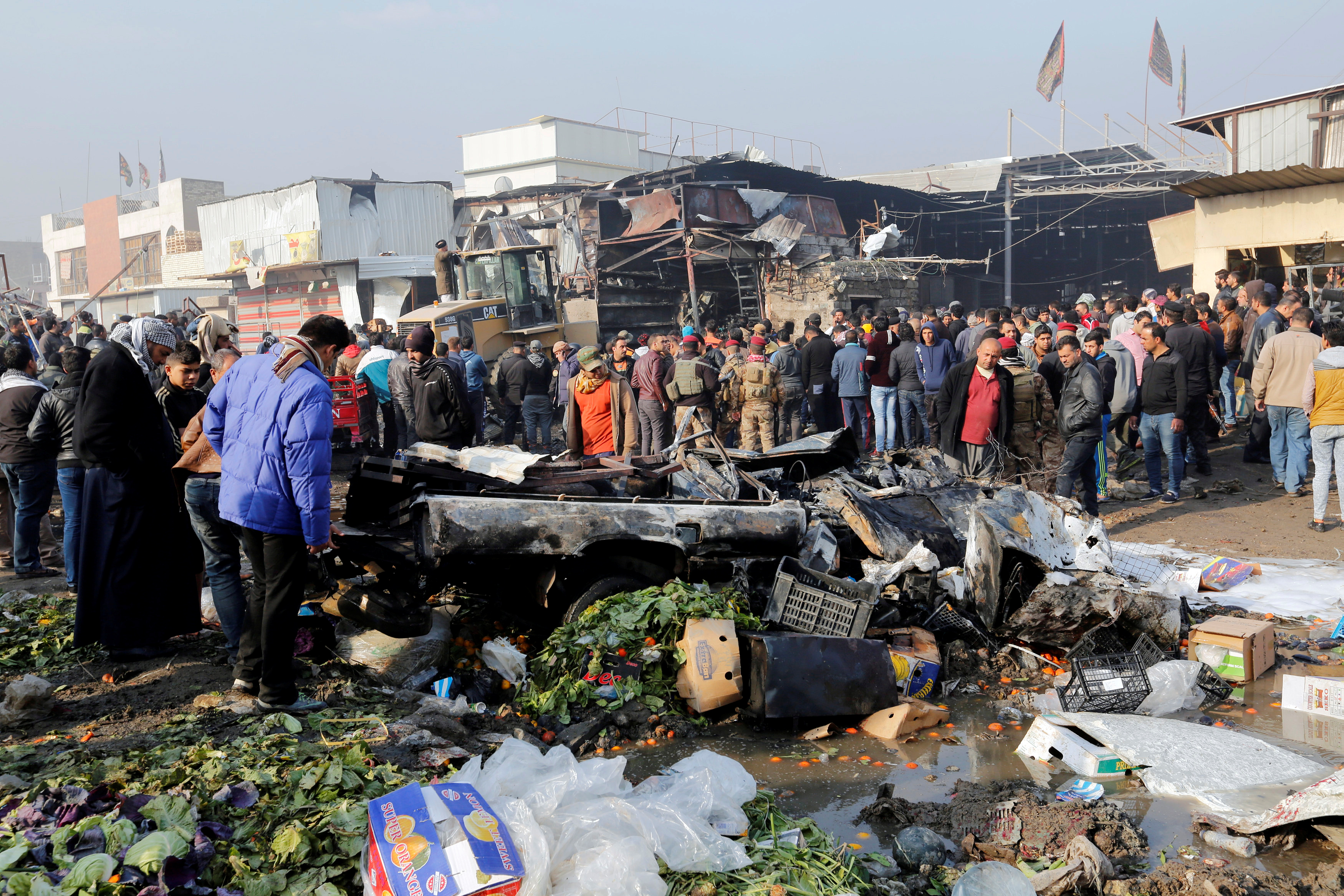 People gather at the site of a car bomb attack at a vegetable market in eastern Baghdad, Iraq Jan. 8, 2017.
