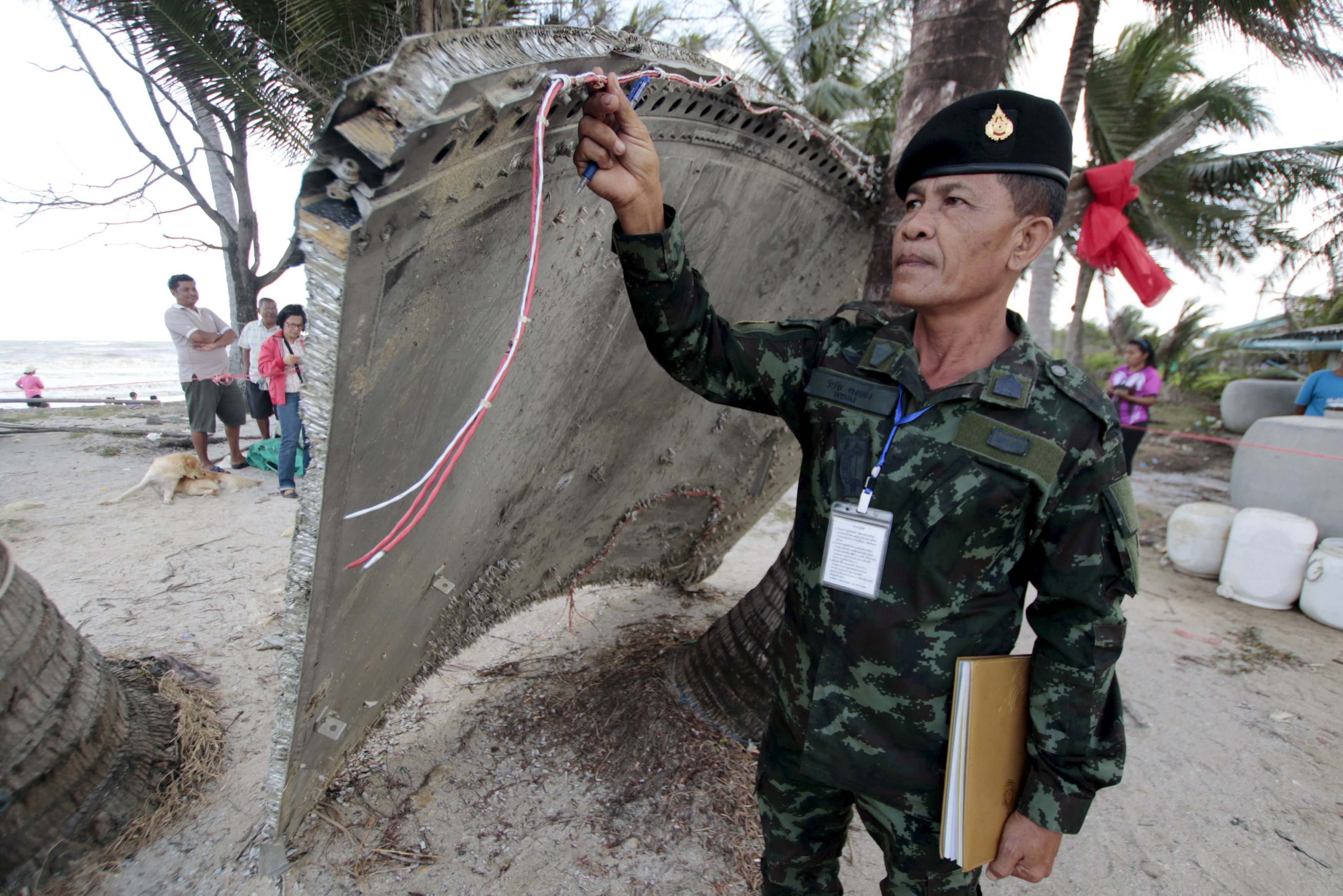 Thai army soldier inspects a piece of suspected plane wreckage which has been found off the coast of southern Thailand in Nakhon Si Thammarat province, Jan. 24, 2016.