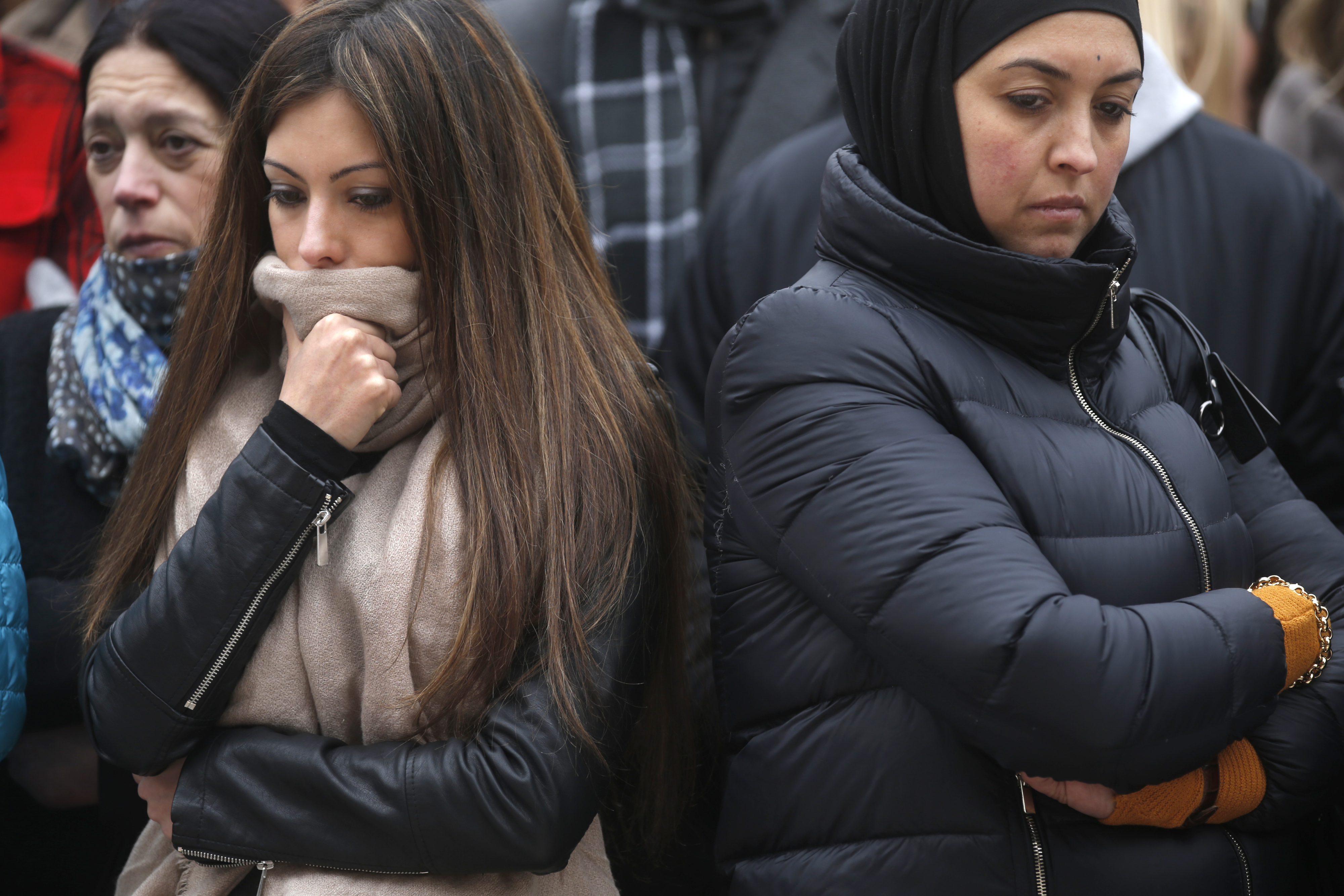People observe a minute of silence at a street memorial to victims of Tuesday's bombings in Brussels, Belgium, March 24, 2016.