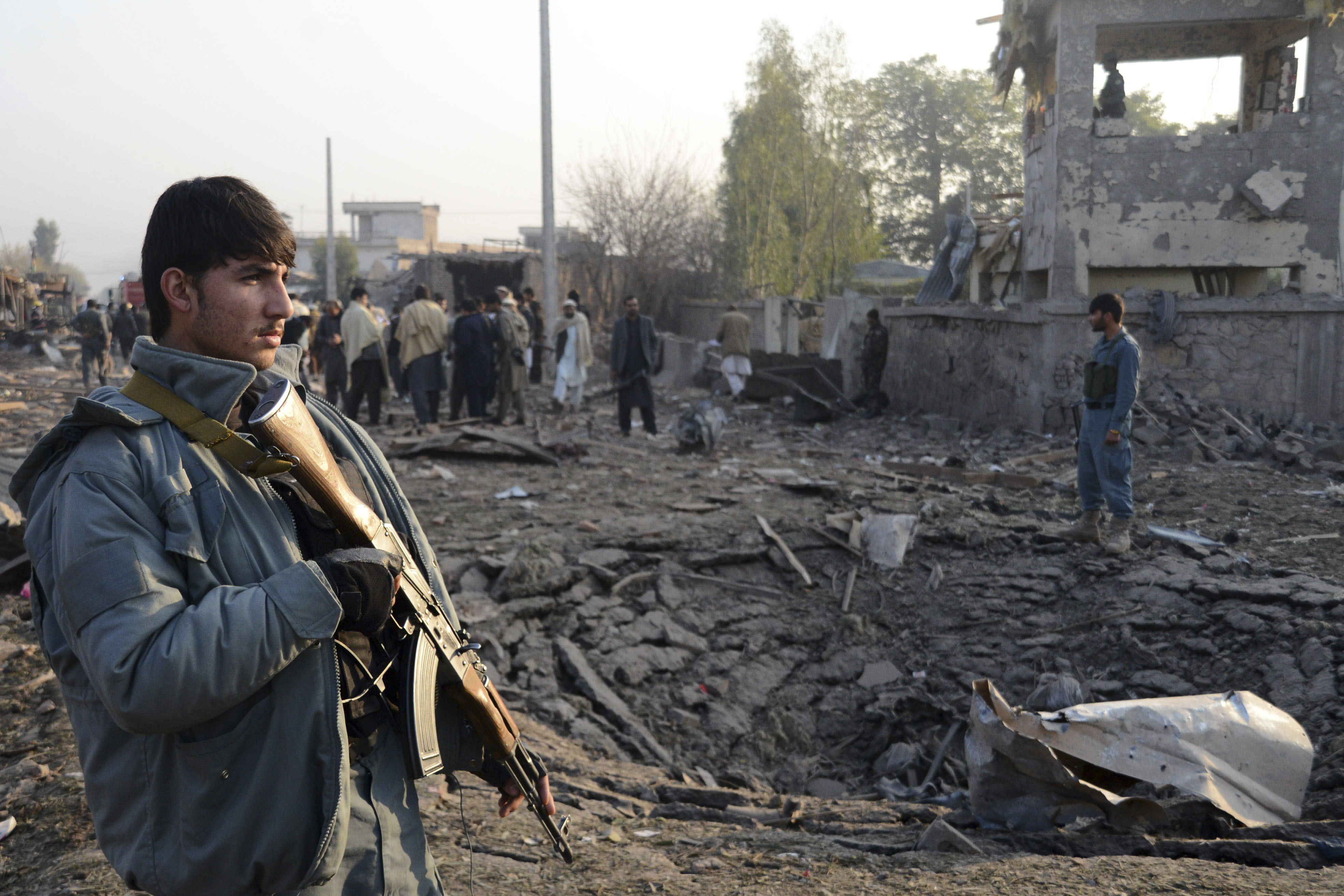 Afghan security members inspect the site of a suicide car bombing at Surkh Rud district in Nangarhar province, east of Kabul, Afghanistan, Dec. 7, 2015.
