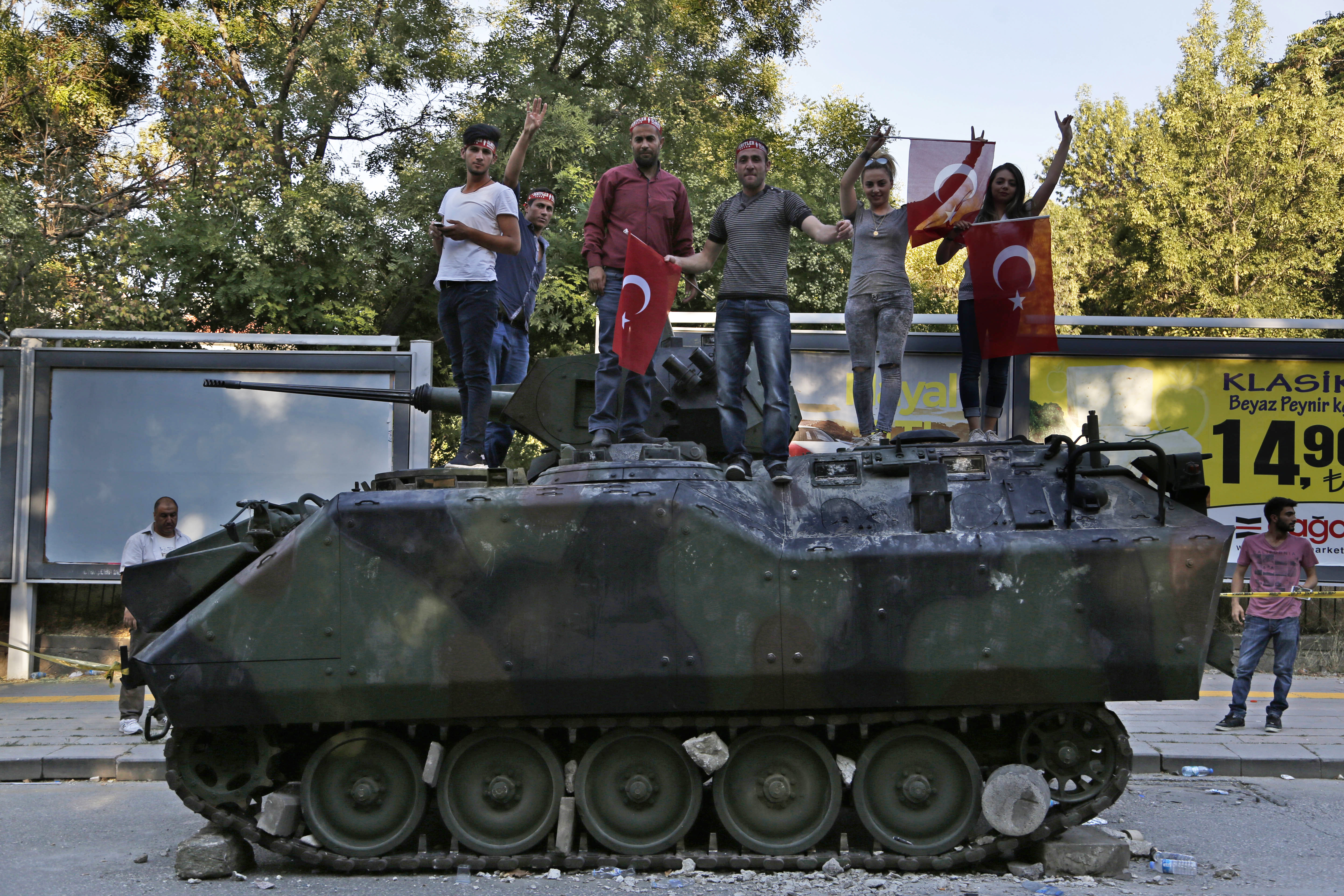 Turkish citizens stand on a damaged Turkish military armored personnel carrier  that was attacked by protesters in a street near the Turkish military headquarters in Ankara, July 16, 2016.