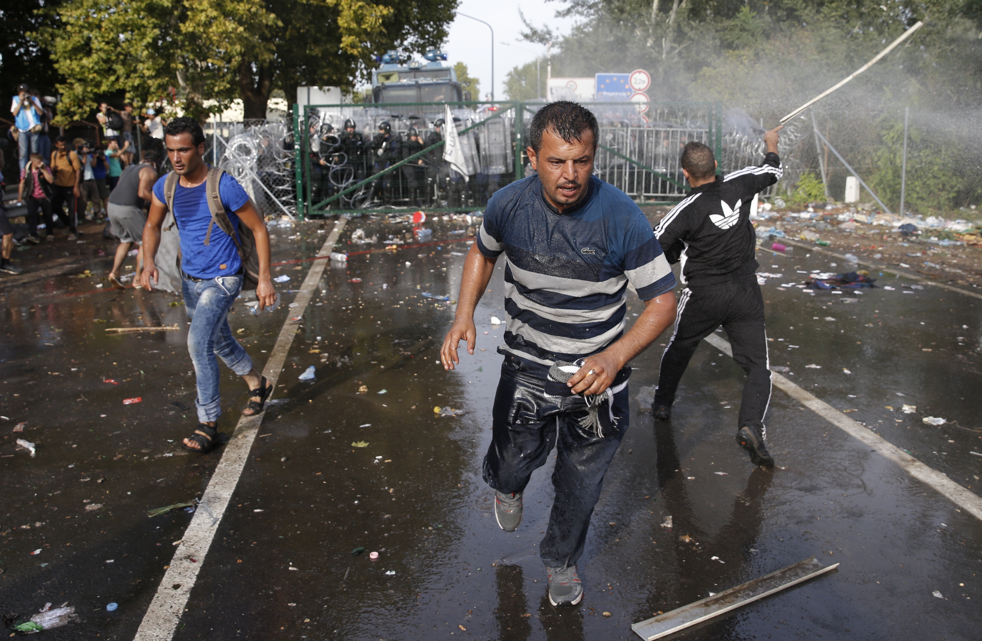 Migrants run as Hungarian riot police fires tear gas and water cannon at the border crossing with Serbia in Roszke, Hungary, Sept. 16, 2015.