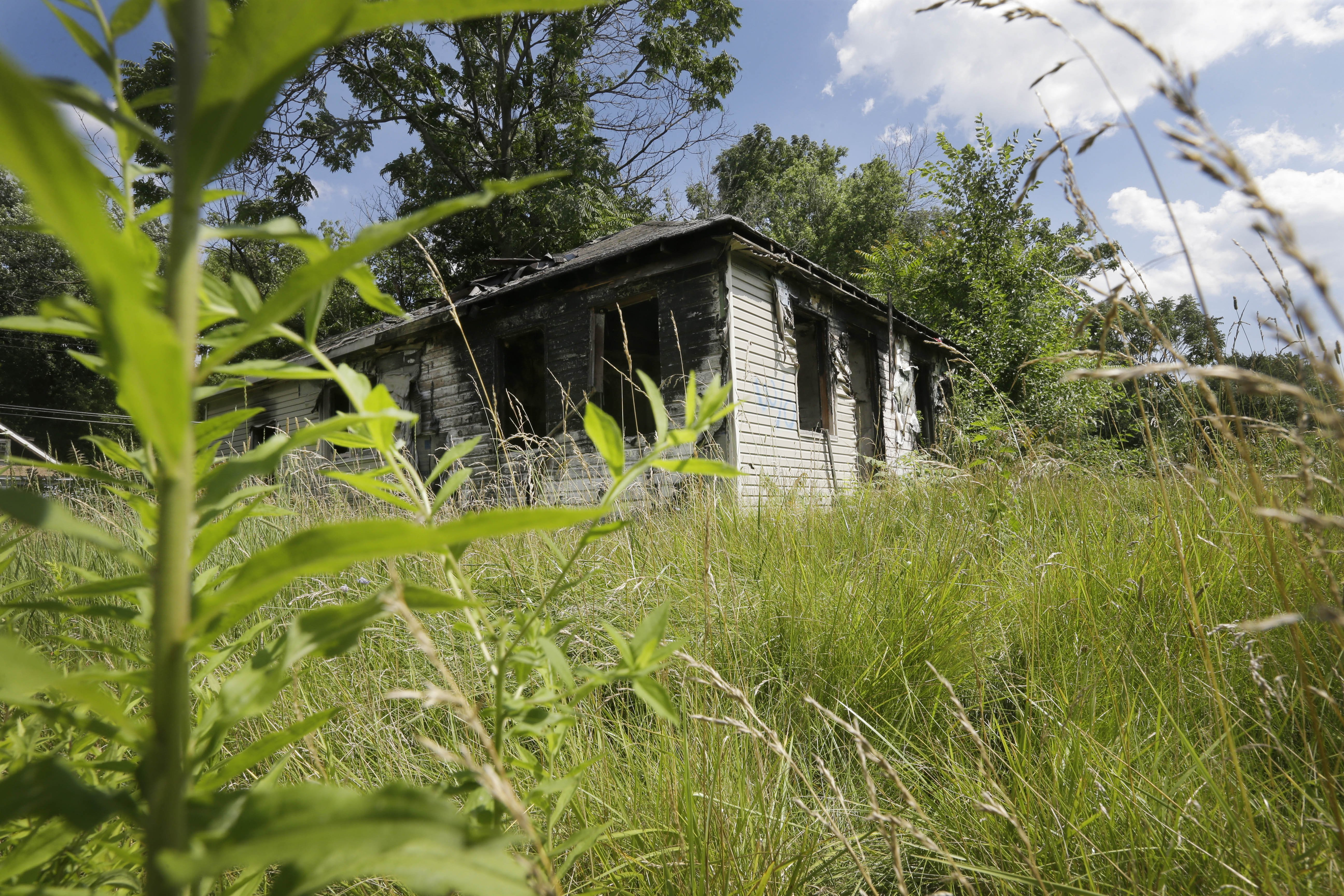 FILE - An abandoned house with an overgrown lot is seen in Brightmoor, a neighborhood on Detroit's northwest side, July 19, 2013. Brightmoor is one of the city's more blighted neighborhoods and improving Brightmoor is a battle a local activist ha...