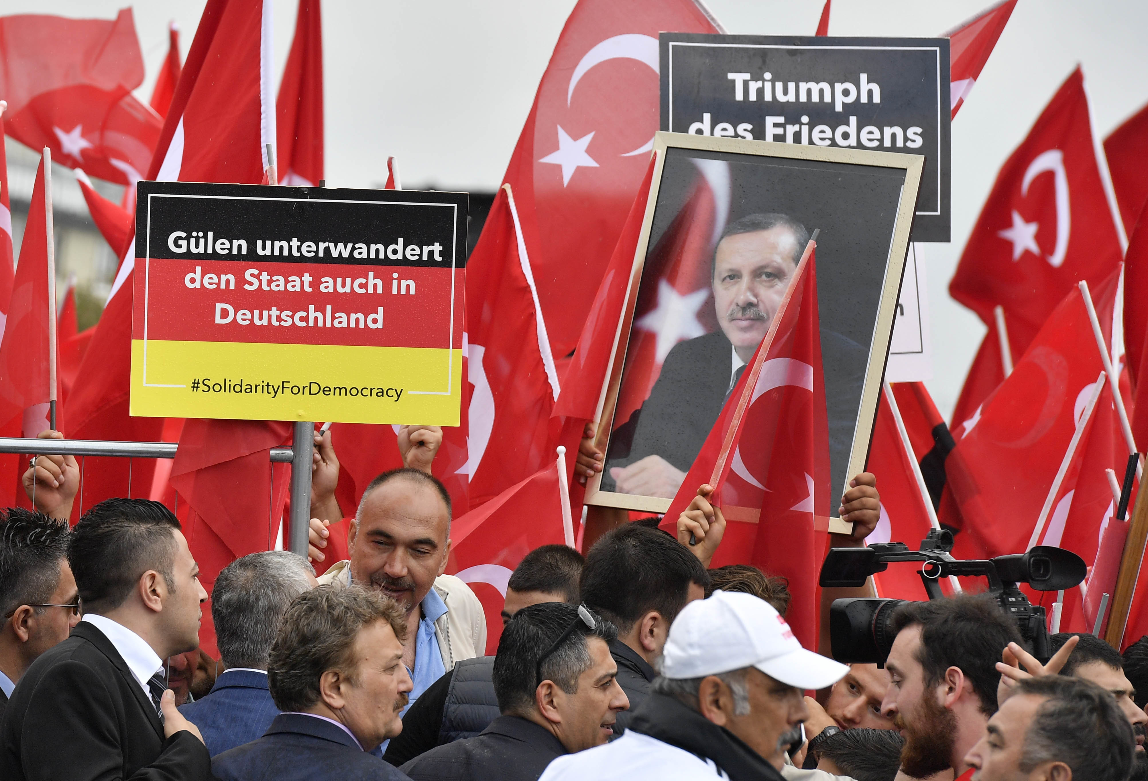 FILE - Turkish protestors hold a banner reading 'Gulen infiltrers the state also in Germany' during a demonstration  in Cologne, Germany, July 31, 2016.
