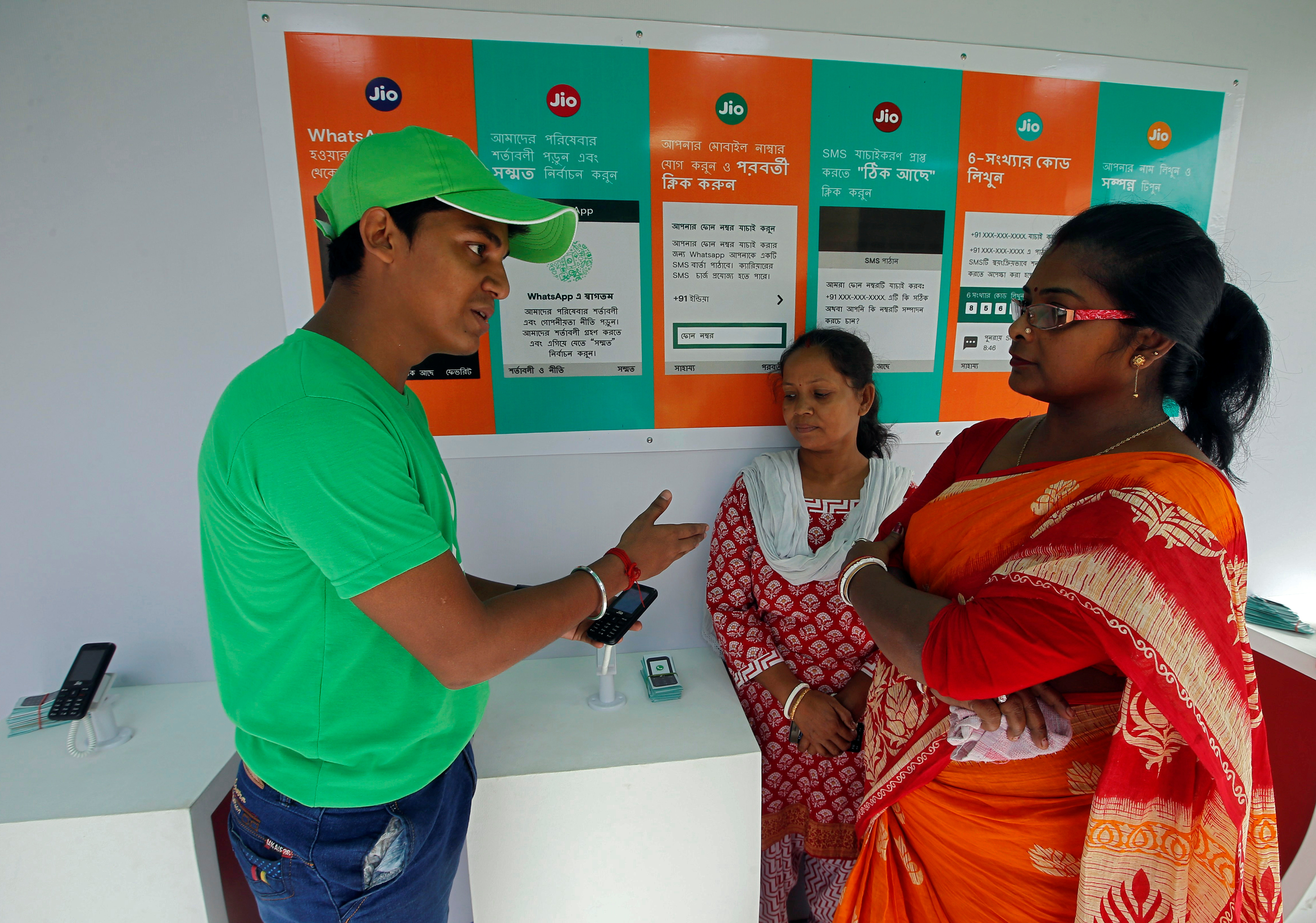 FILE - A WhatsApp-Reliance Jio representative explains how to use Facebook Inc's WhatsApp messenger to a woman during a drive by the two companies to educate users, on the outskirts of Kolkata, India, Oct. 9, 2018.