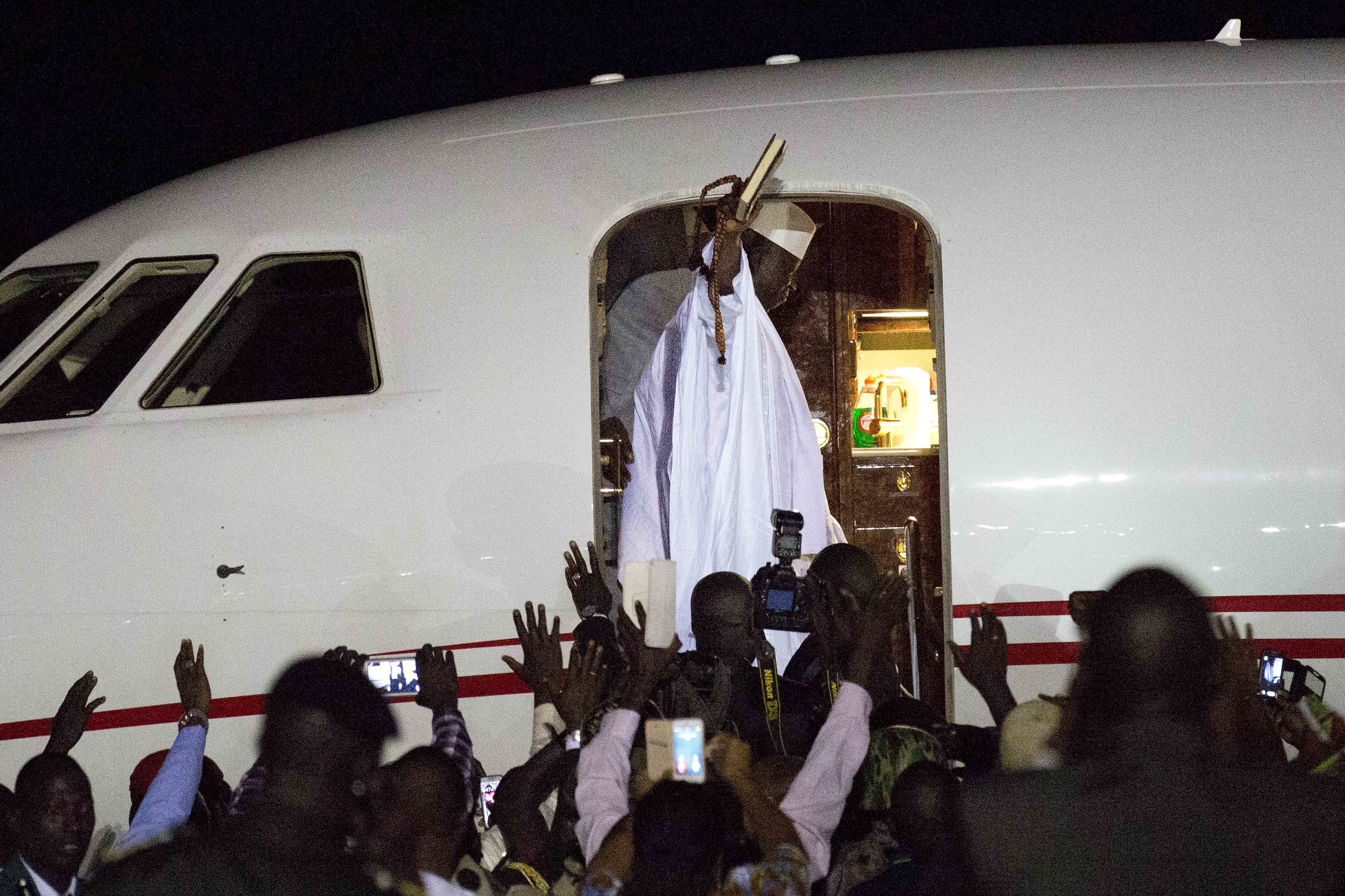 Gambia's defeated leader Yahya Jammeh waves to supporters as he departs from Banjul airport, Jan. 21, 2017.