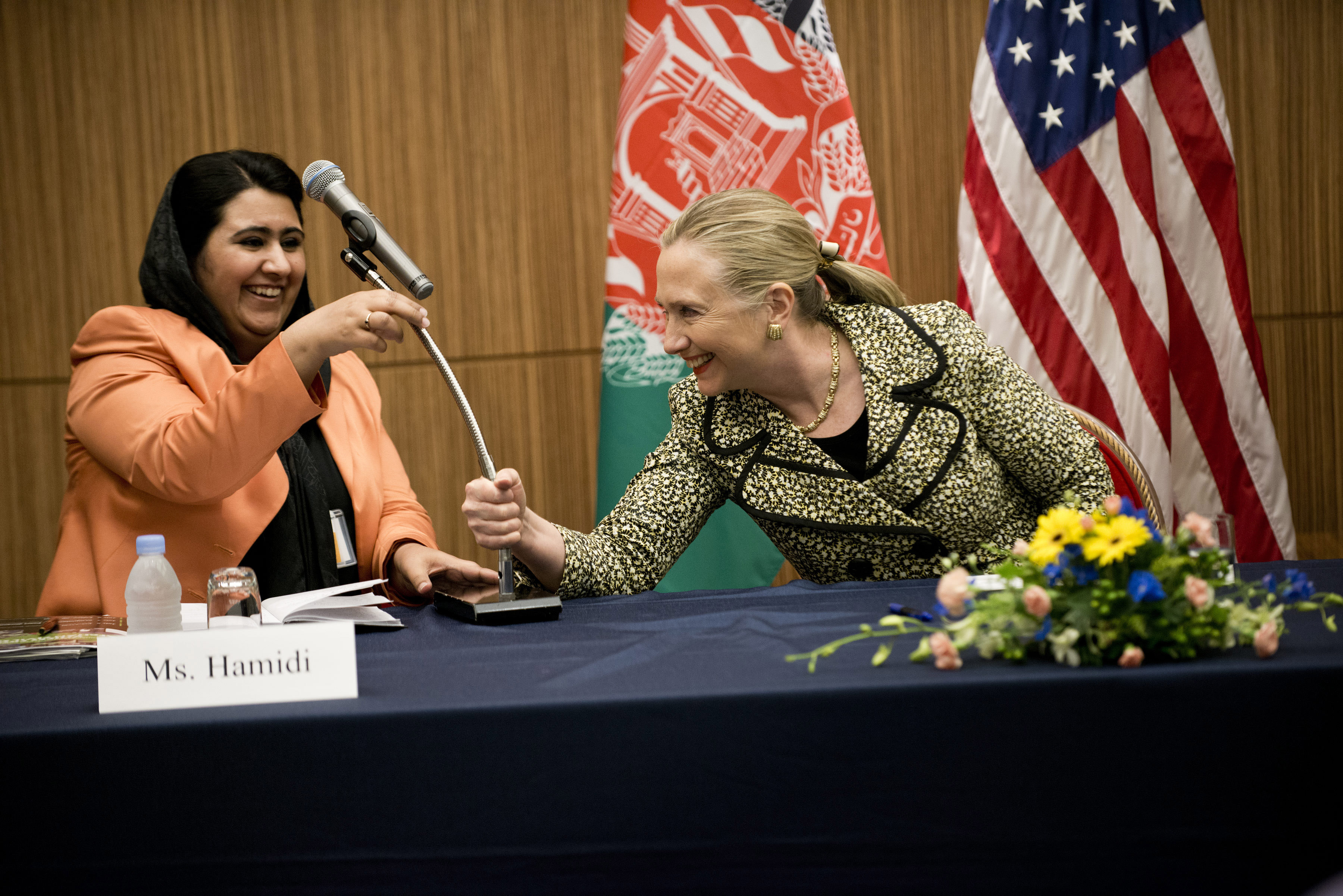 FILE - U.S. Secretary of State Hillary Clinton, right, helps Samira Hamidi, an Afghan rights advocate, with a microphone during the Afghan Civil Society event in Tokyo, July 8, 2012.