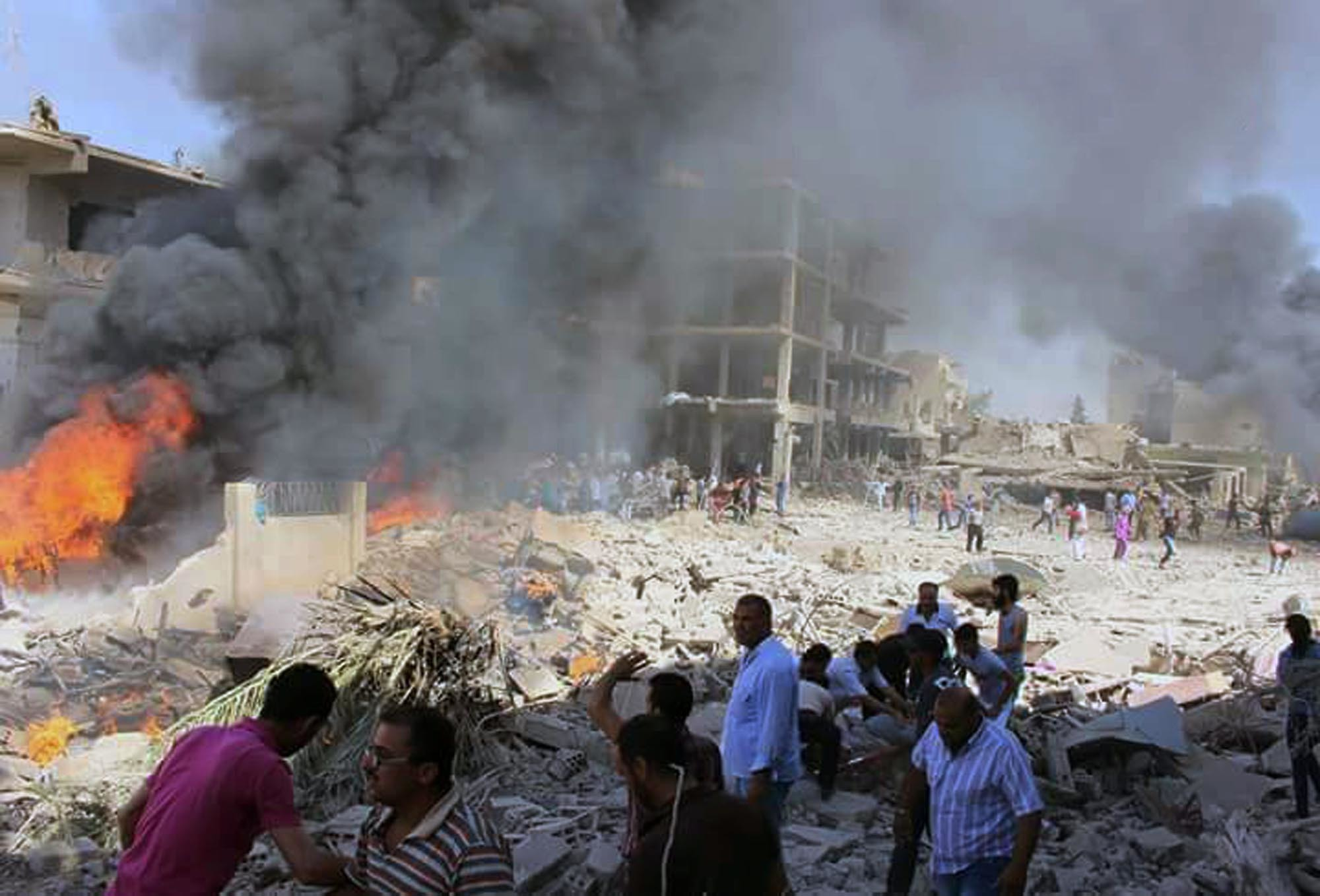 In this photo released by the Syrian official news agency SANA, Syrians gather at the scene where twin bombings struck Kurdish town of Qamishli, Syria, July 27, 2016.