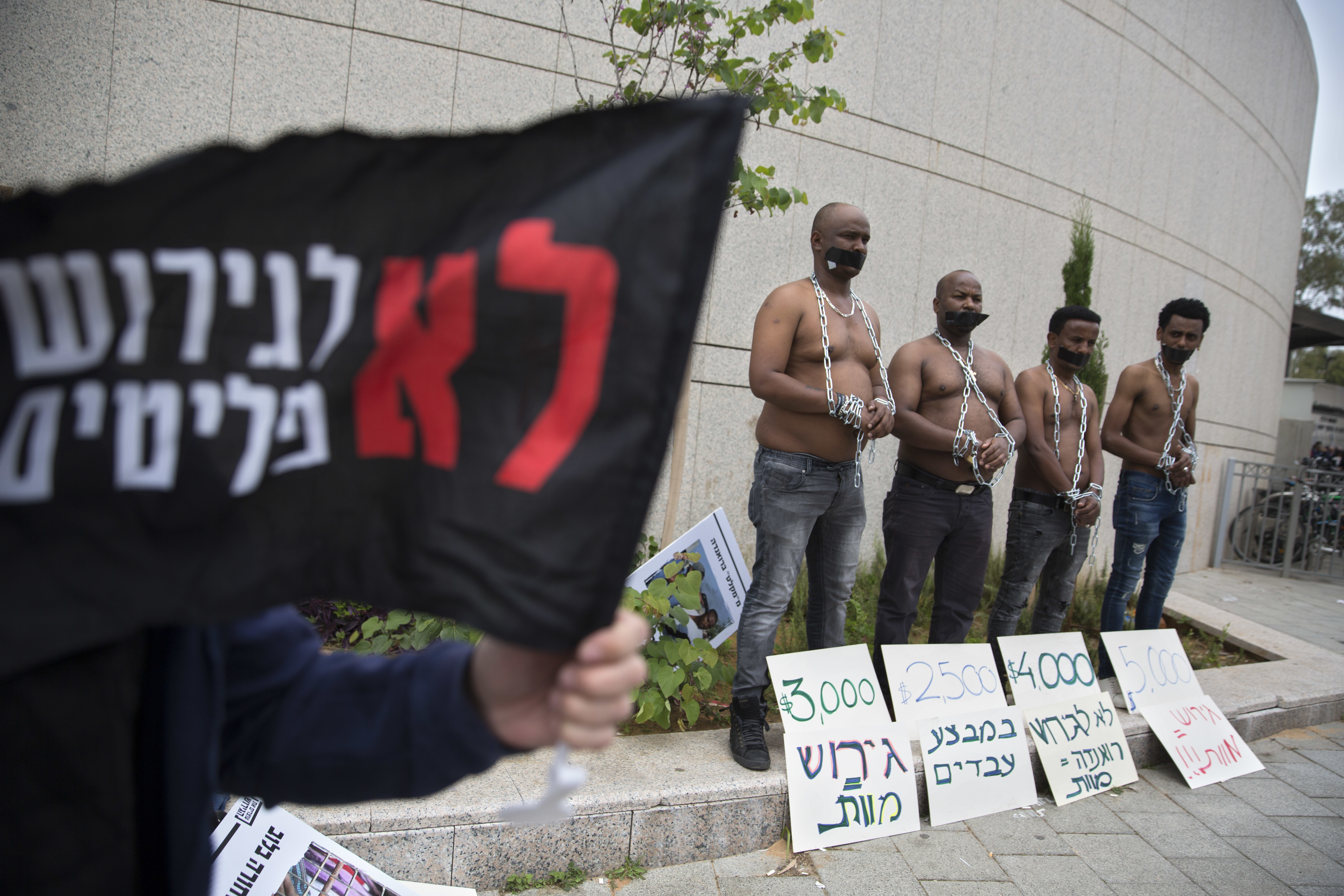 African migrants wear chains to represent slavery during a demonstration in Tel Aviv, Israel, April 3, 2018.