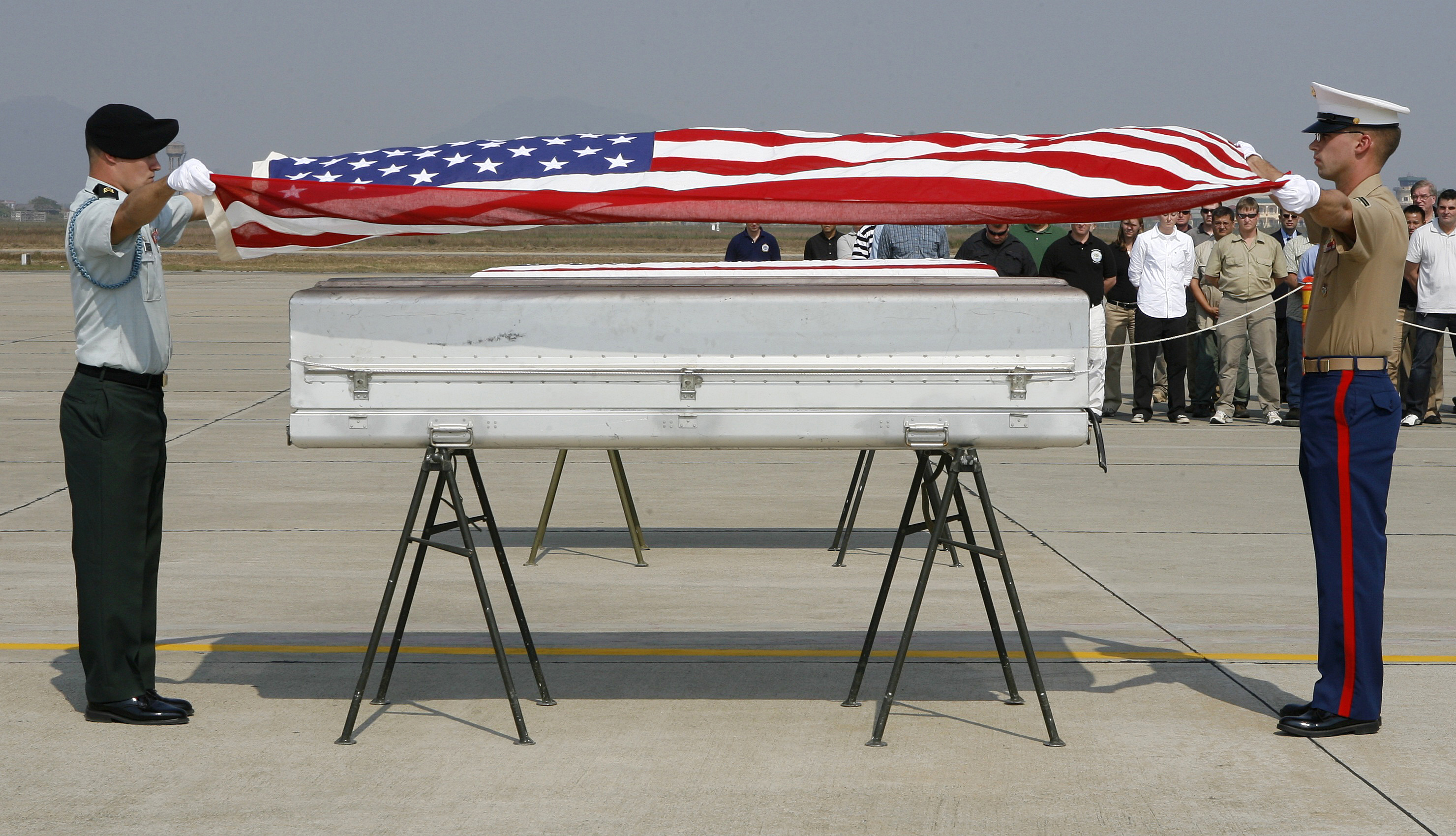 U.S. military personnel drape a U.S. flag over a coffin containing human remains believed to be a U.S serviceman missing in action during the Vietnam War, at a repatriation ceremony at Hanoi's Noi Bai airport December 9, 2008.  Four cases of human re...