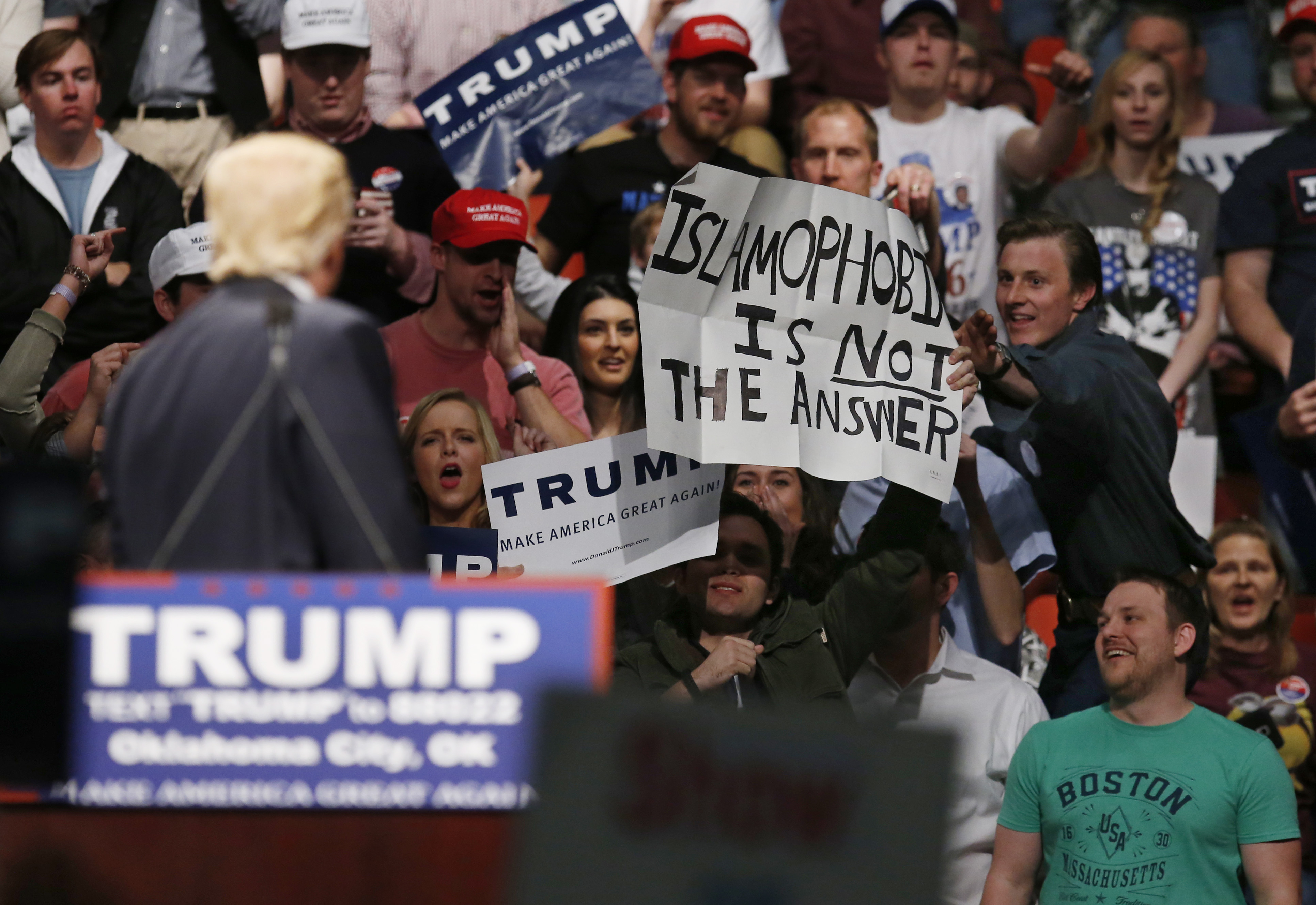 """FILE - Republican presidential candidate Donald Trump, left, looks on as one of his supporter reaches for a sign that reads """"Islamophobia is not the answer,"""" at a rally in Oklahoma City, Feb. 26, 2016."""