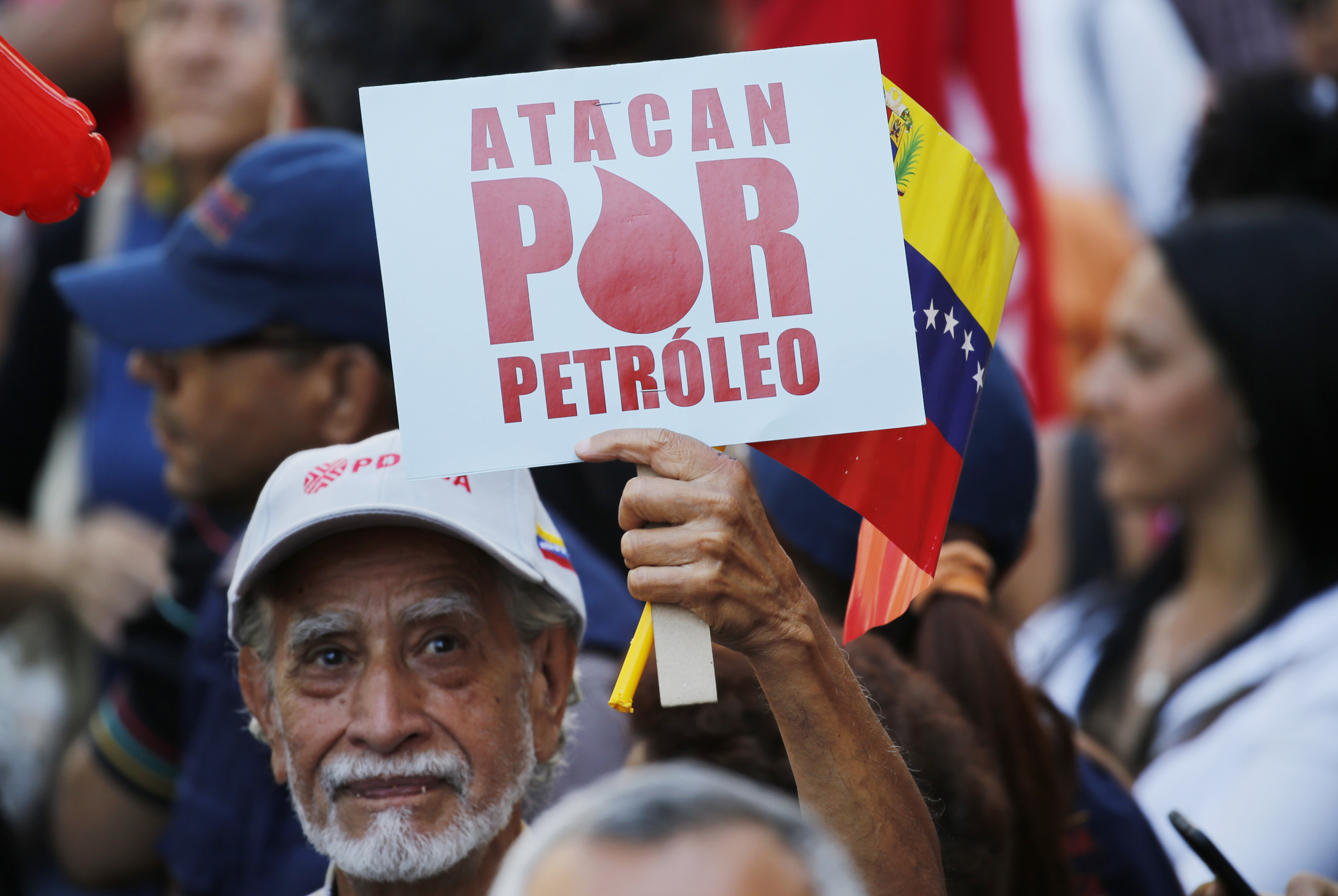 "A man holds a sign that reads in Spanish ""They attack for oil"" during a march of in support of the state-run oil company PDVSA, in Caracas, Venezuela, Jan. 31, 2019."