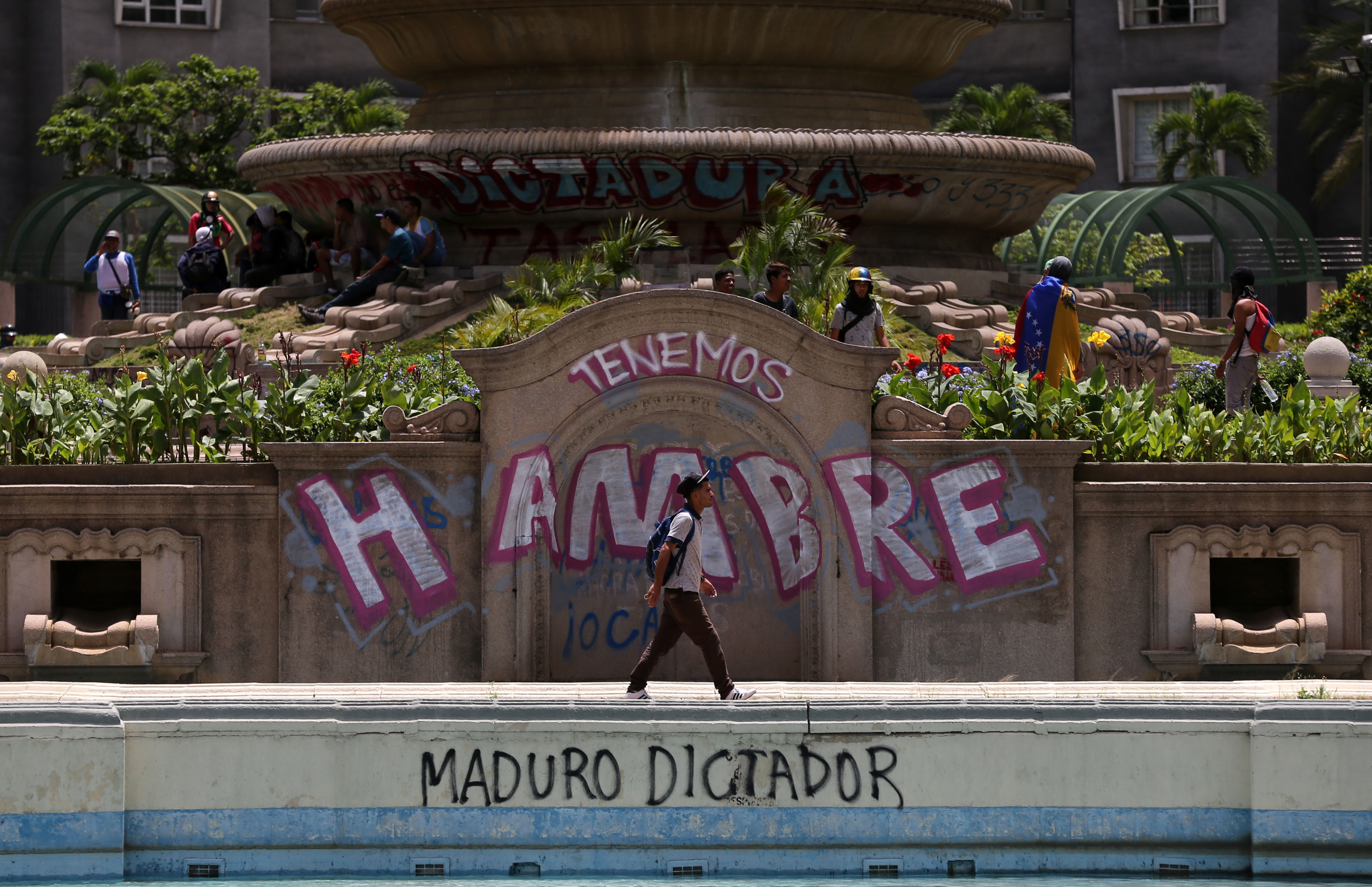 """Anti-government protesters begin gathering at Altamira Plaza, defaced with messages that read in Spanish; """"We're hungry. Maduro Dictator,"""" in Caracas, Venezuela, June 26, 2017."""