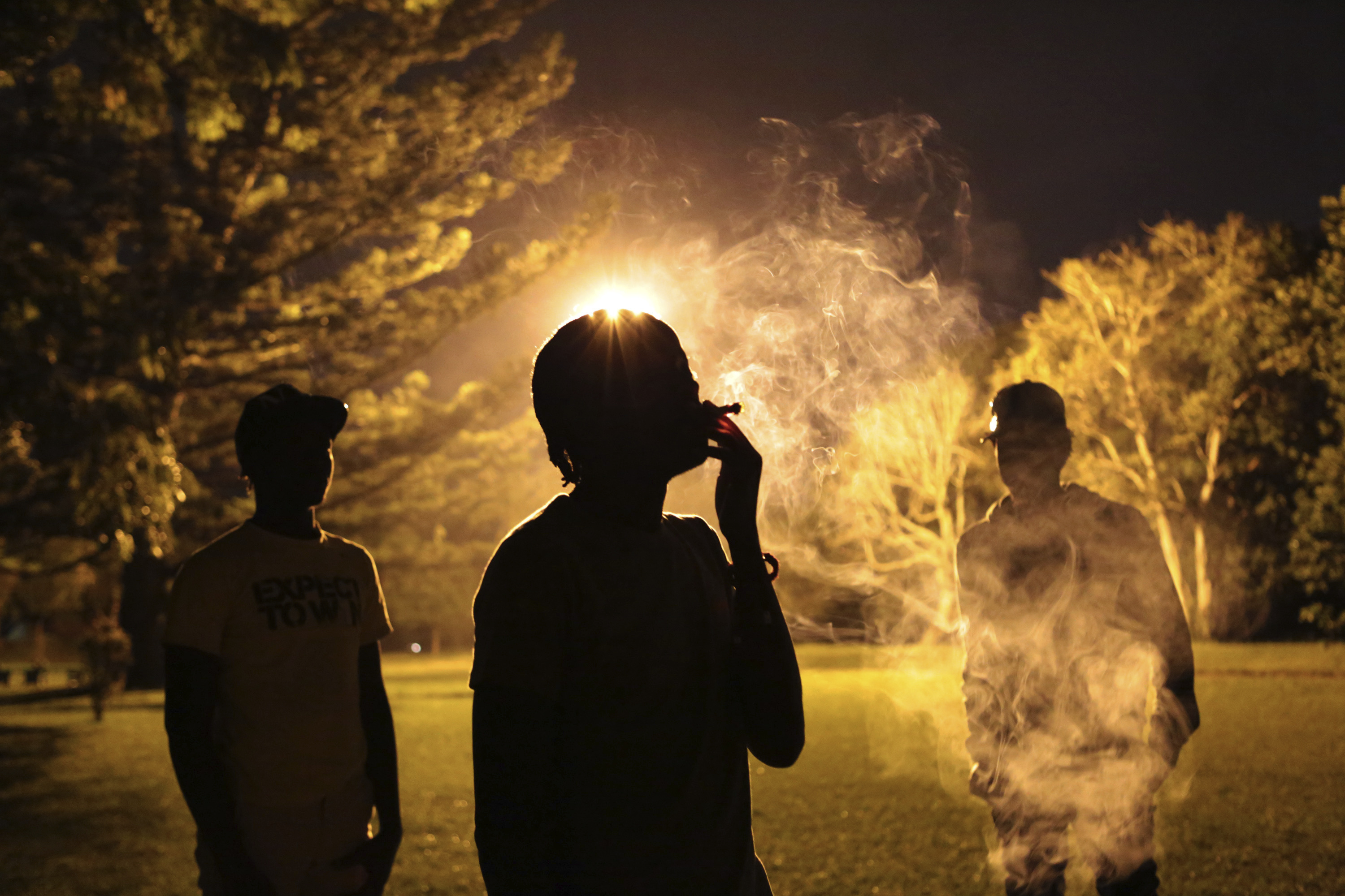 Youths take turns to smoke marijuana in a park in Harare, Zimbabwe, May, 4, 2018.