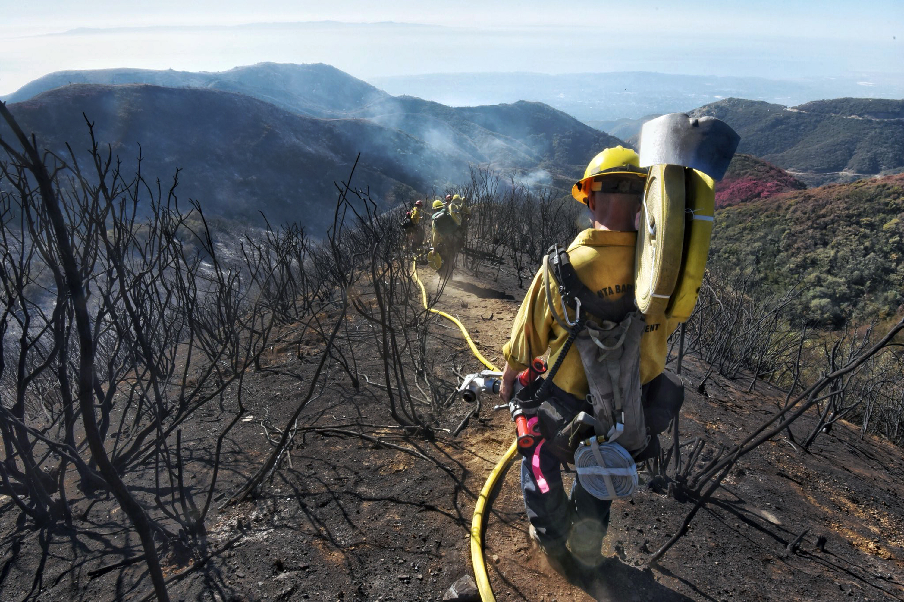 In this photo provided by the Santa Barbara County Fire Department, Santa Barbara County Firefighters haul dozens of pounds of hose and equipment down steep terrain below E. Camino Cielo to root out and extinguish smoldering hot spots in Santa Barbar...