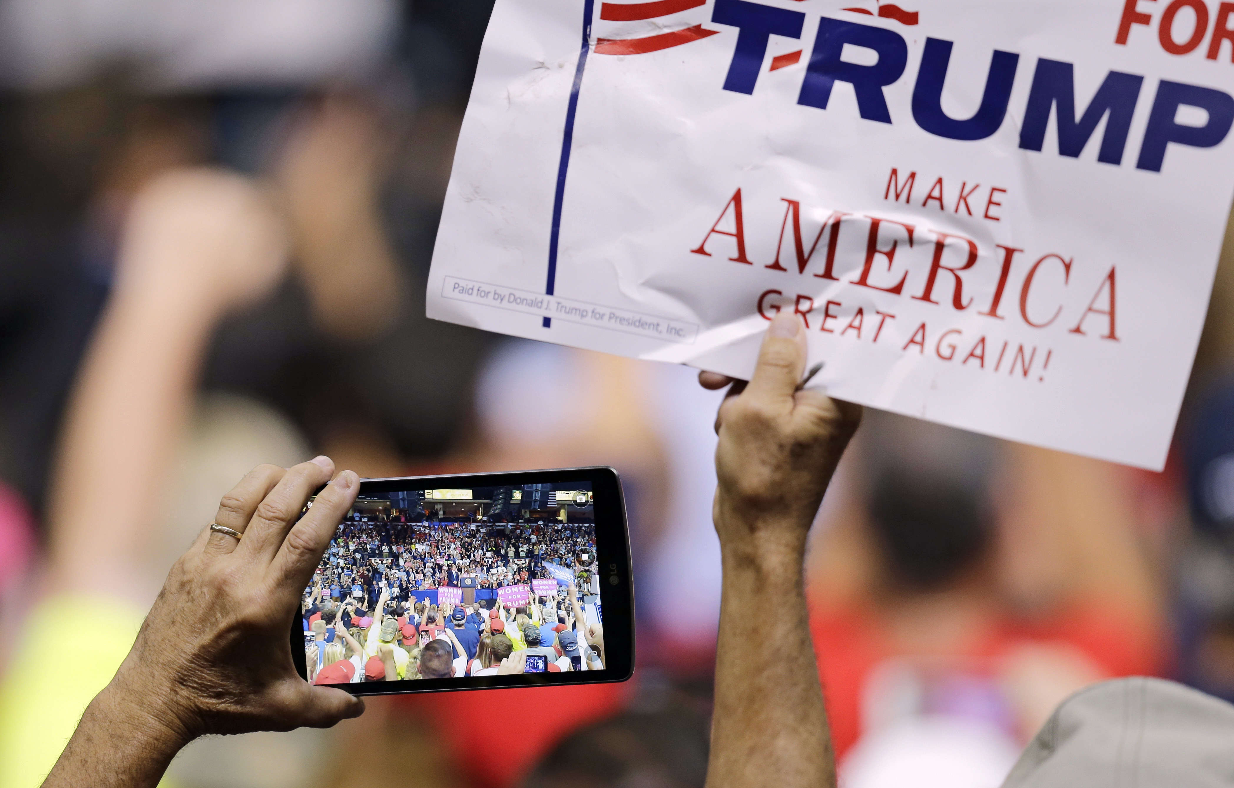 FILE - A supporter holds up a sign and records on his phone as President Donald Trump speaks.