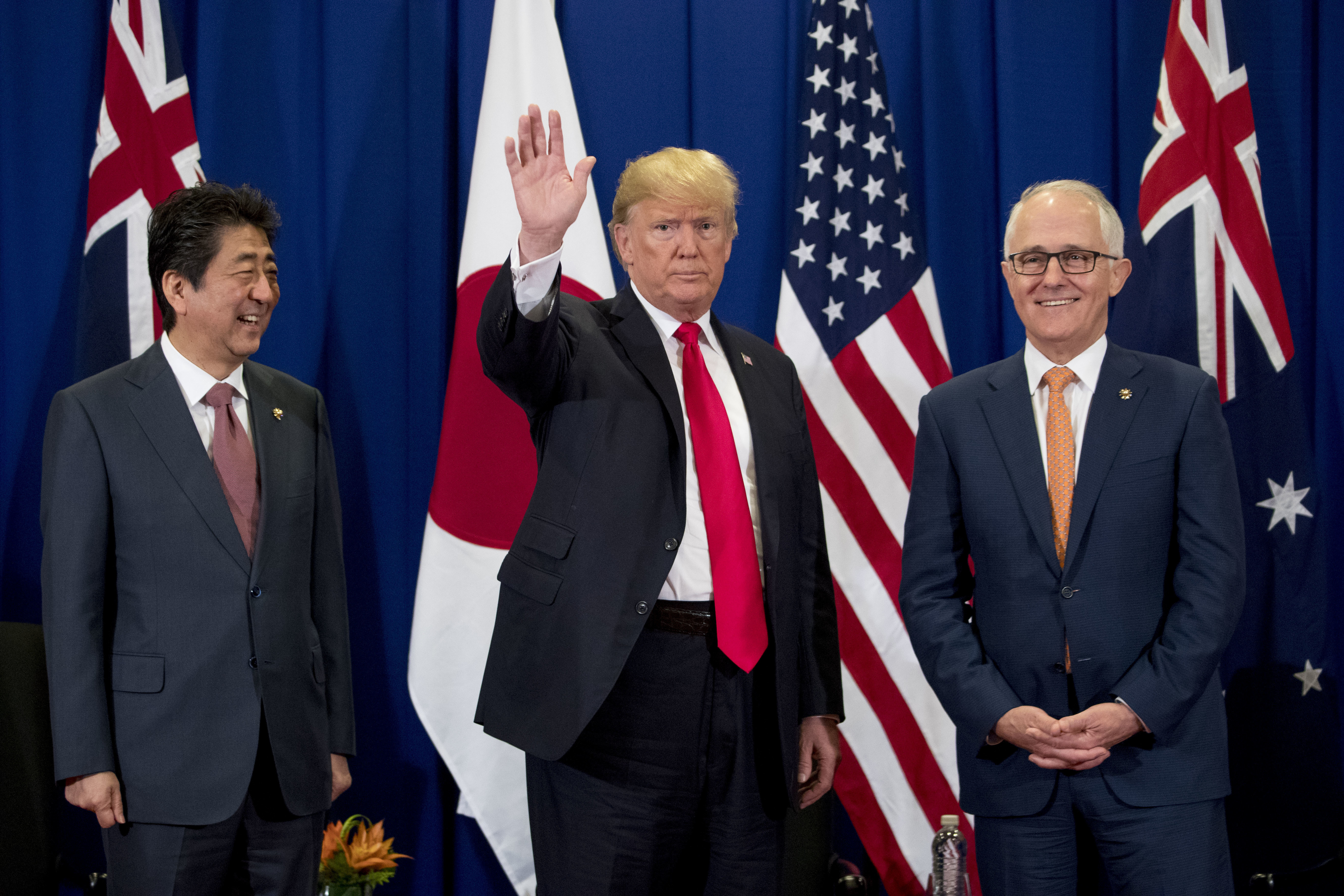 President Donald Trump, accompanied by Japanese Prime Minister Shinzo Abe, left, and Australian Prime Minister Malcolm Turnbull, right, waves to reporters at a meeting during the ASEAN Summit at the Sofitel Philippine Plaza, Monday, Nov. 13, 2017, in...
