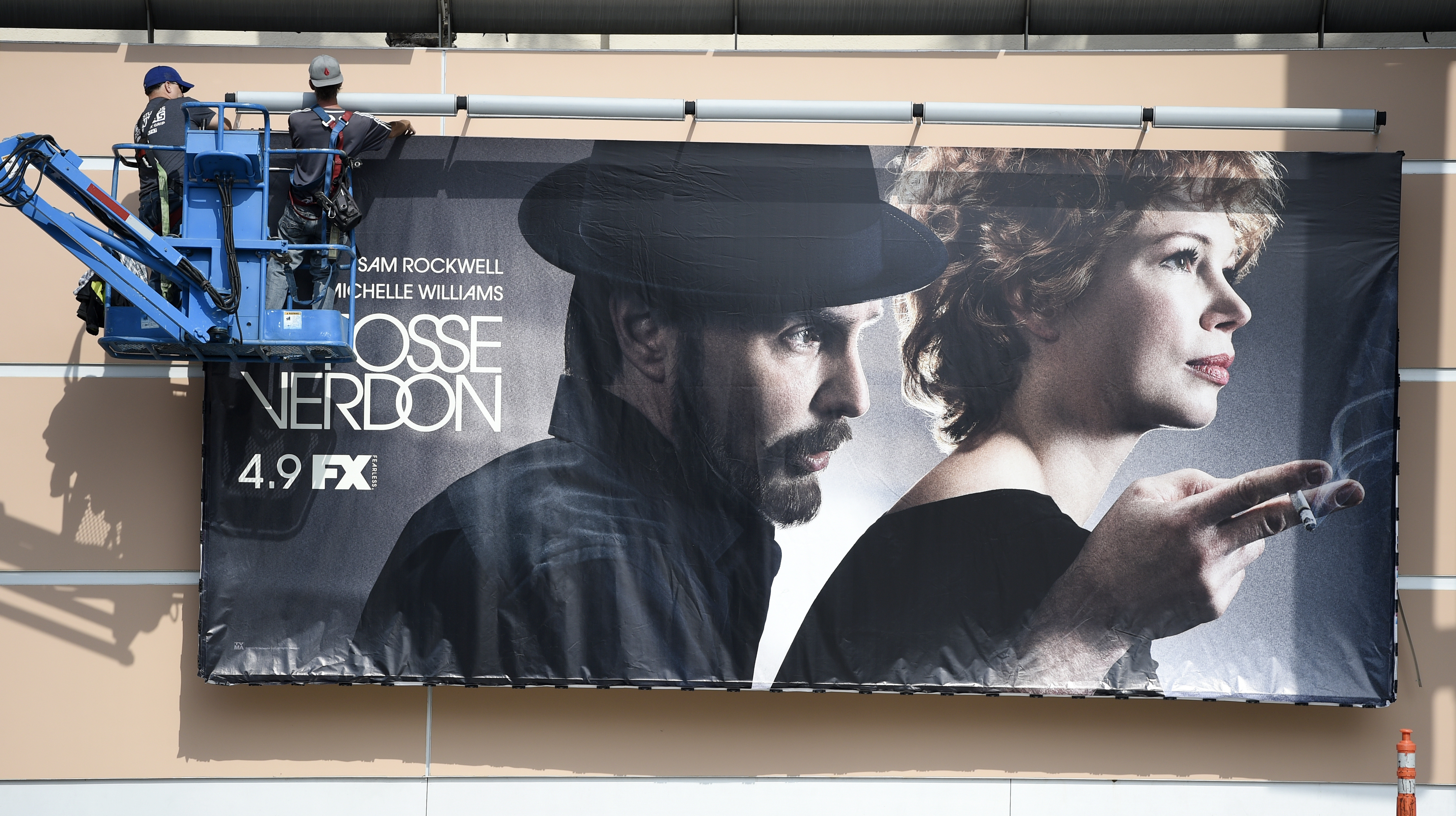 "Workers put up a poster for the upcoming FX limited series ""Fosse/Verdon"" near the entrance to Fox Studios, March 19, 2019, in Los Angeles."