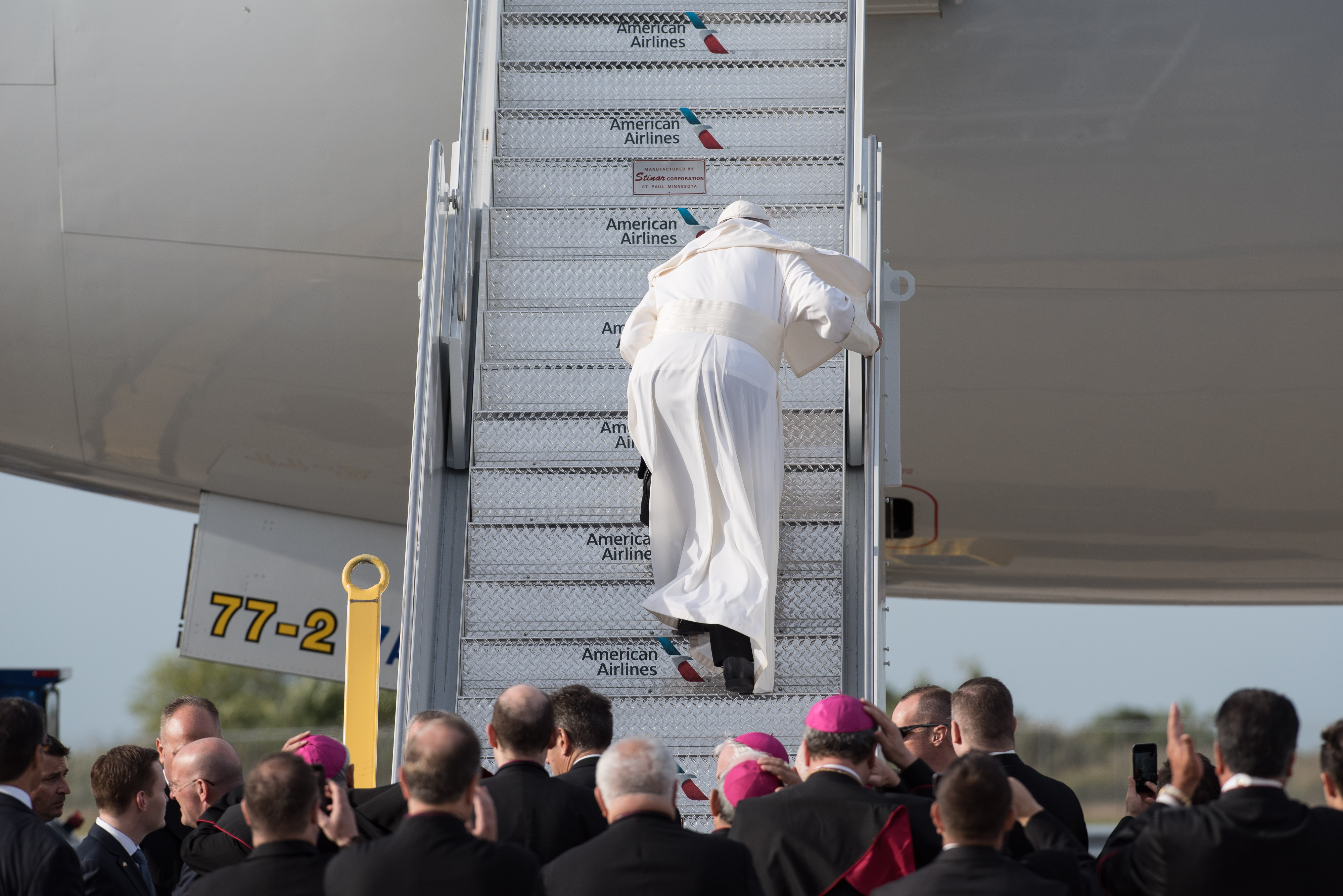 Pope Francis stumbles up the stairs to his flight from New York en route to Philadelphia from John F. Kennedy International Airport in New York, Sept. 26, 2015.