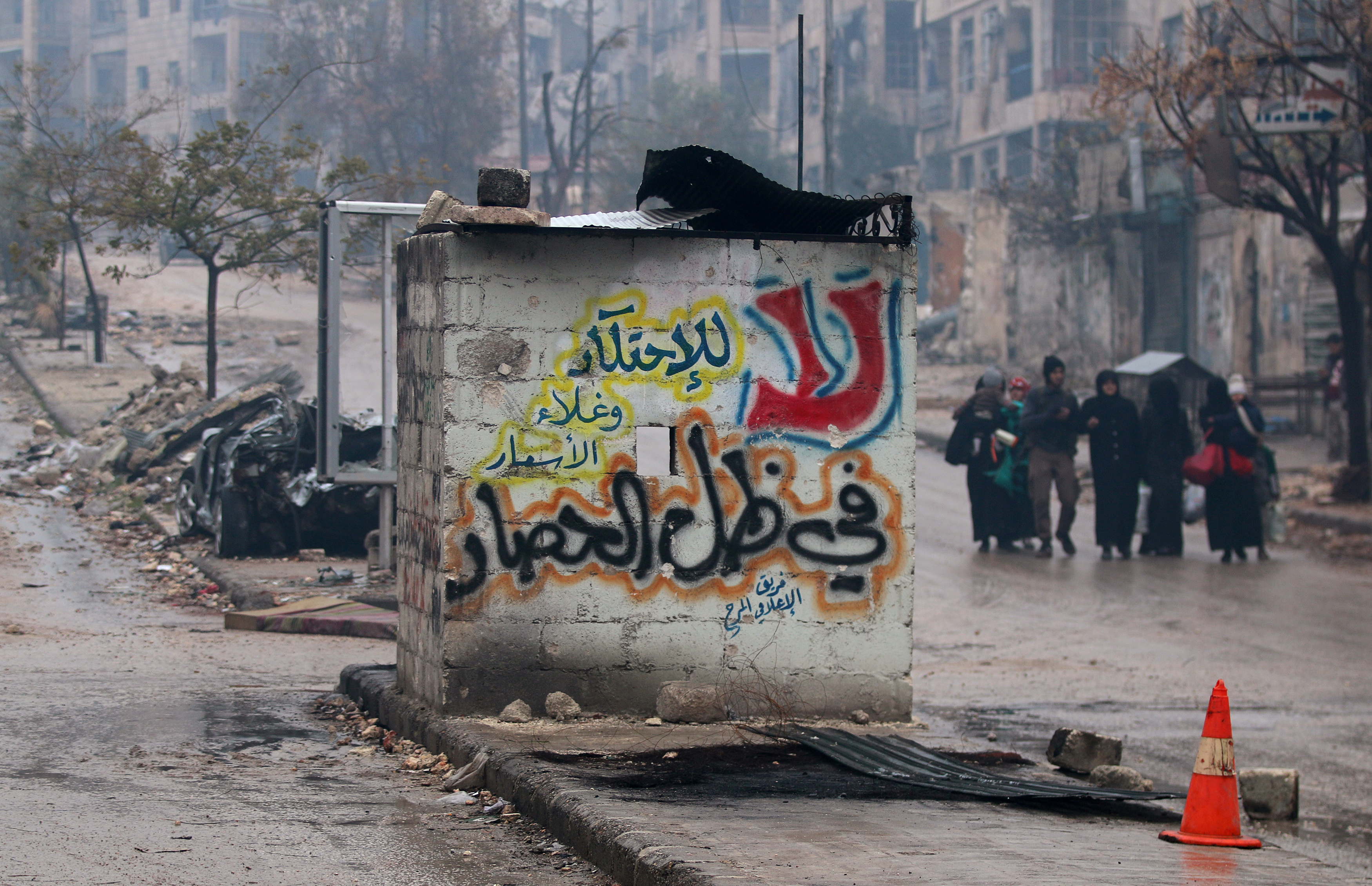 """People carry their belongings as they flee deeper into the remaining rebel-held areas of Aleppo, Syria, Dec. 13, 2016. The Arabic words read, """"No to monopolizing commodities and raising prices under the siege."""""""