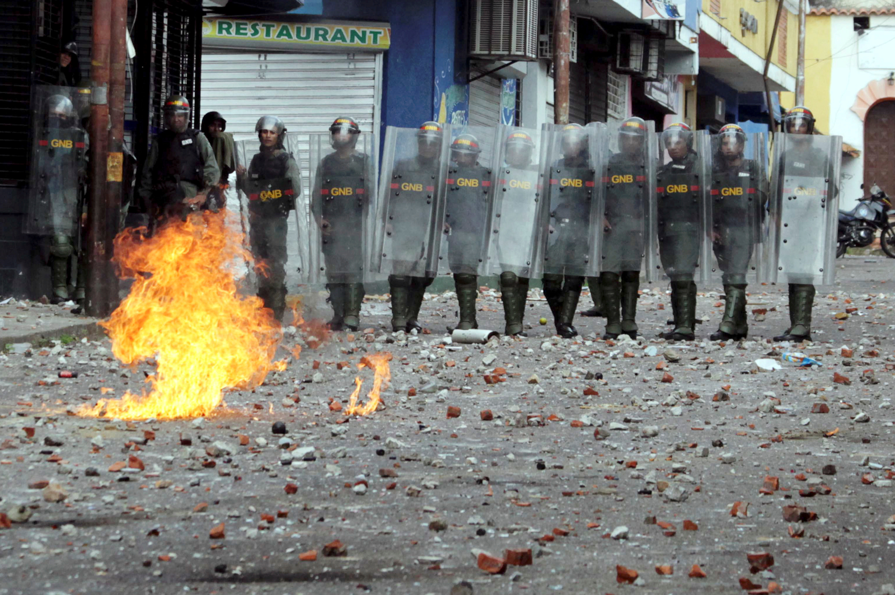 Security forces look on while clashing with opposition supporters participating in a rally against Venezuelan President Nicolas Maduro's government and to commemorate the 61st anniversary of the end of the dictatorship of Marcos Perez Jimenez in Tach...
