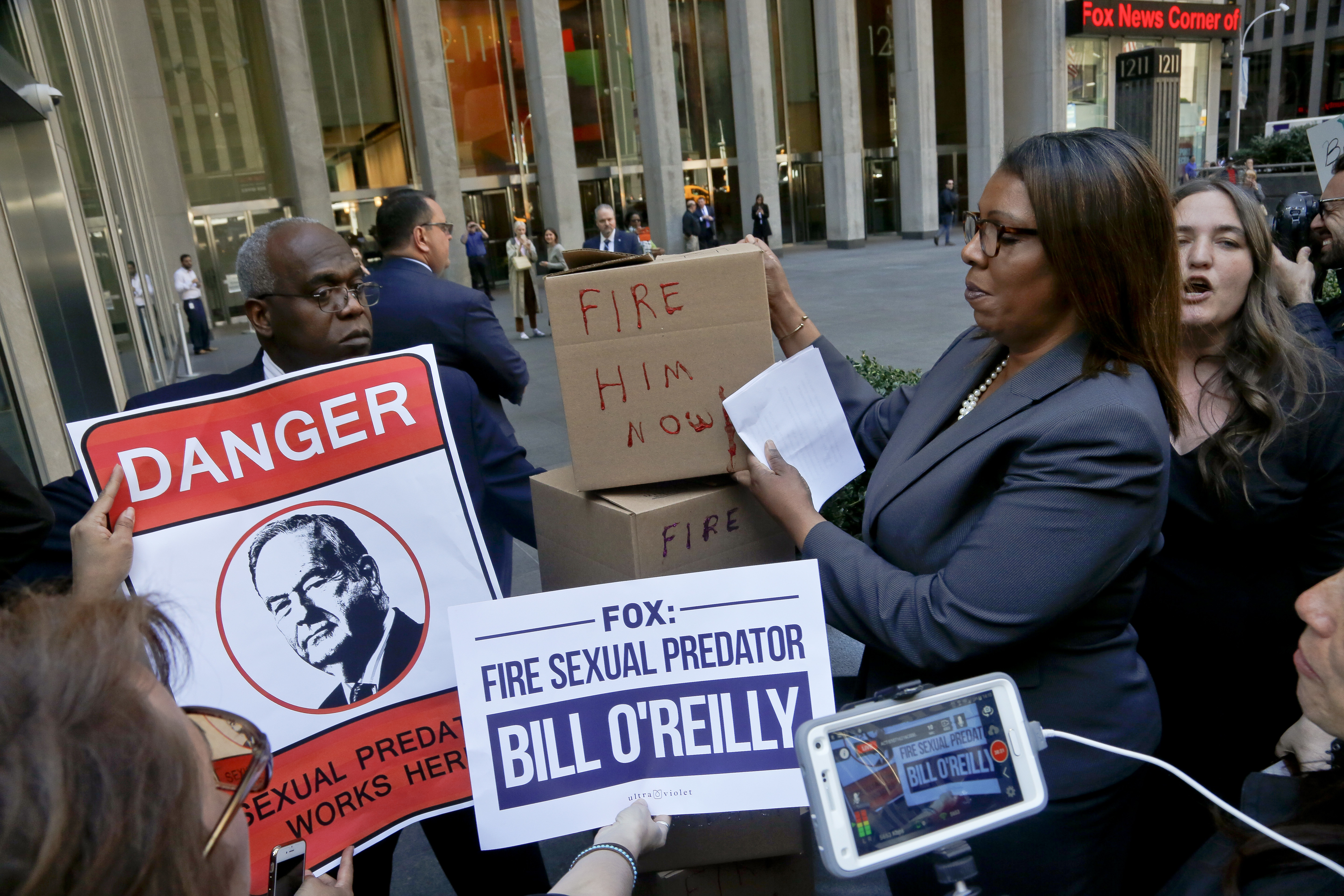 A security guard blocks an entry way as New York Public Advocate Letitia James, second from right, and protesters attempt to deliver boxes of petitions calling for the network to fire Bill O'Reilly, in New York, April 18, 2017.