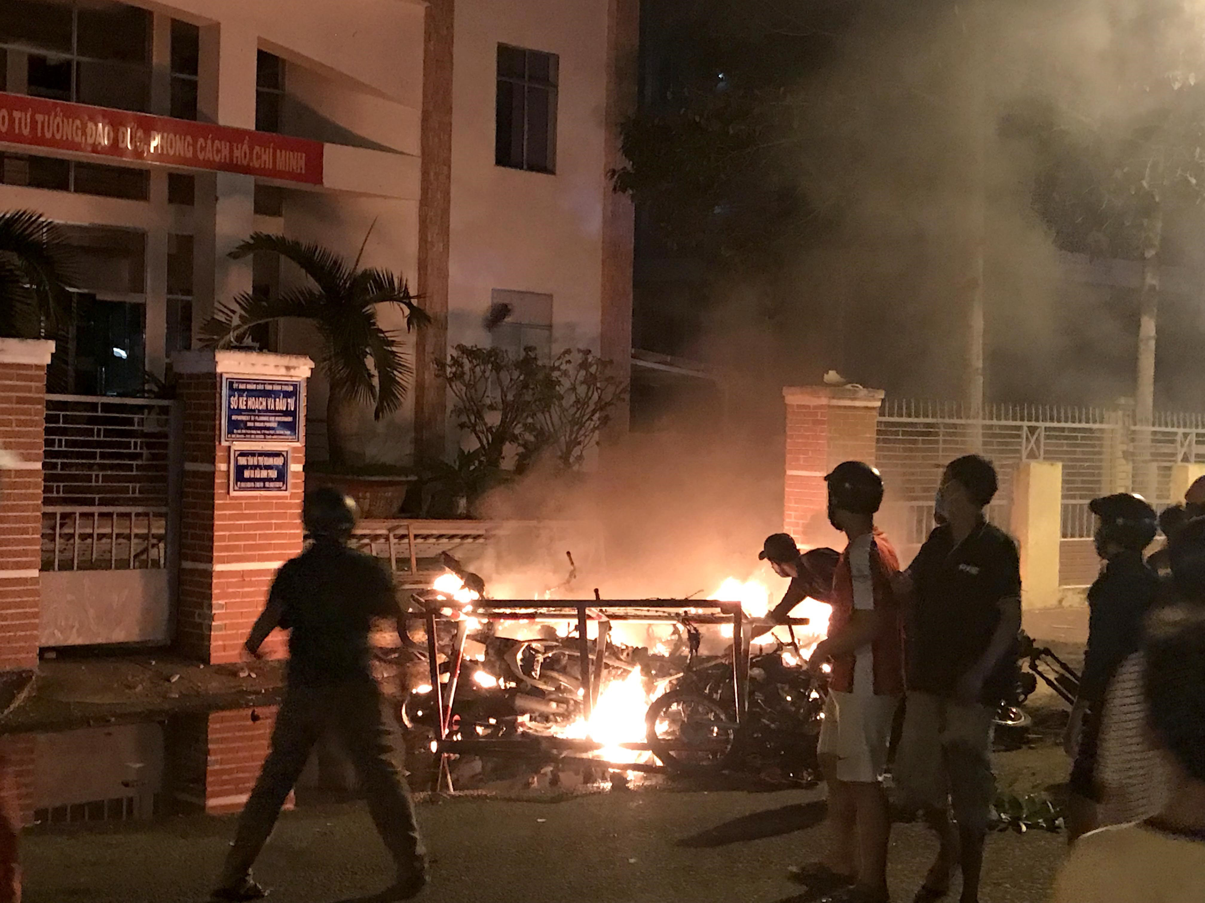 Picture taken on June 10, 2018 shows protesters burning motorcycles in front of a provincial office in Vietnam's south central coast Binh Thuan province in response to legislation on three special economic zones that would grant 99-year leases to com...