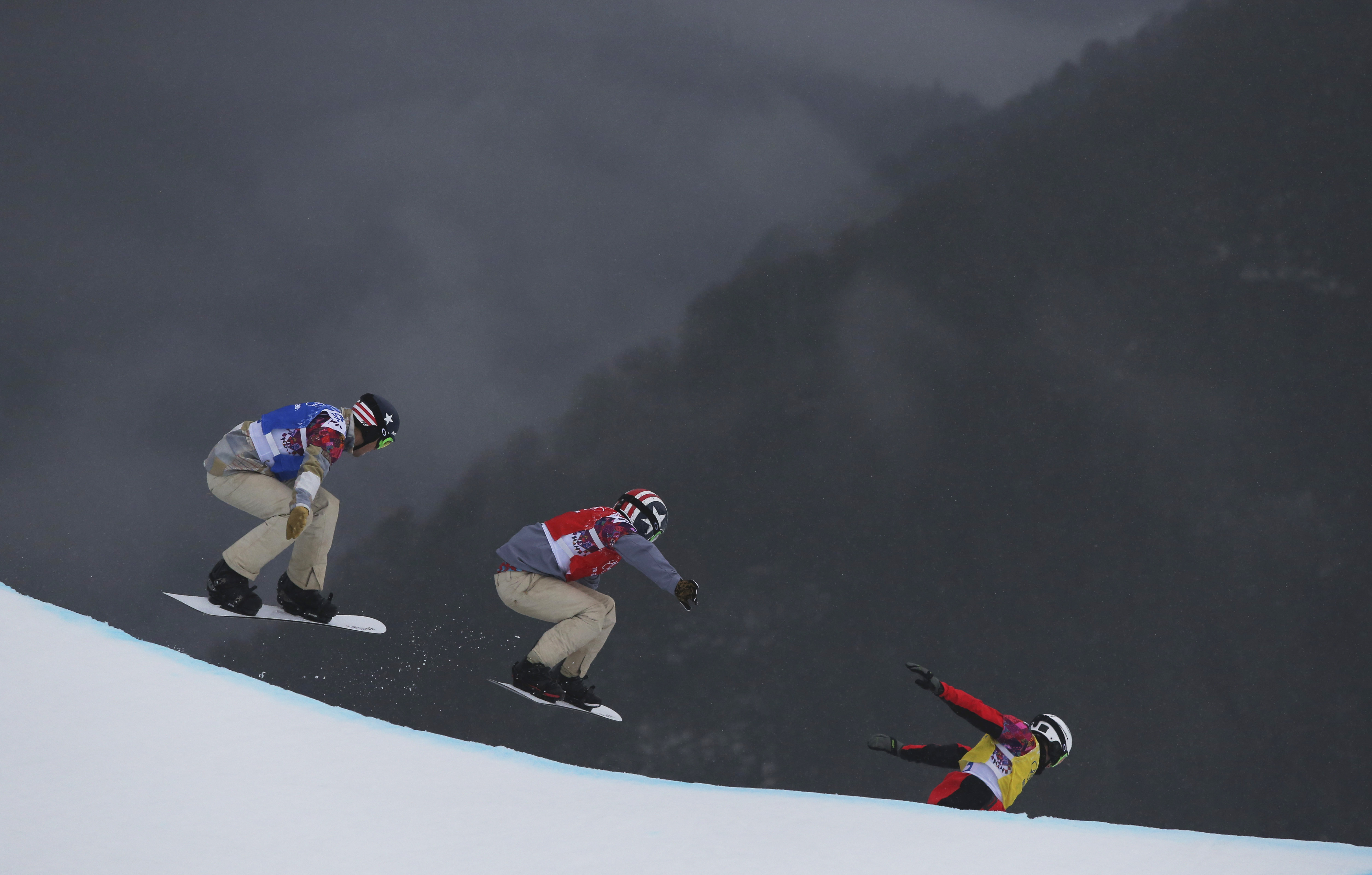 Alex Deibold of the United States, Trevor Jacob of the United States and Norway's Stian Sivertzen go off a drop during the first men's snowboard cross semifinal  at the 2014 Winter Olympics, Feb. 18, 2014.