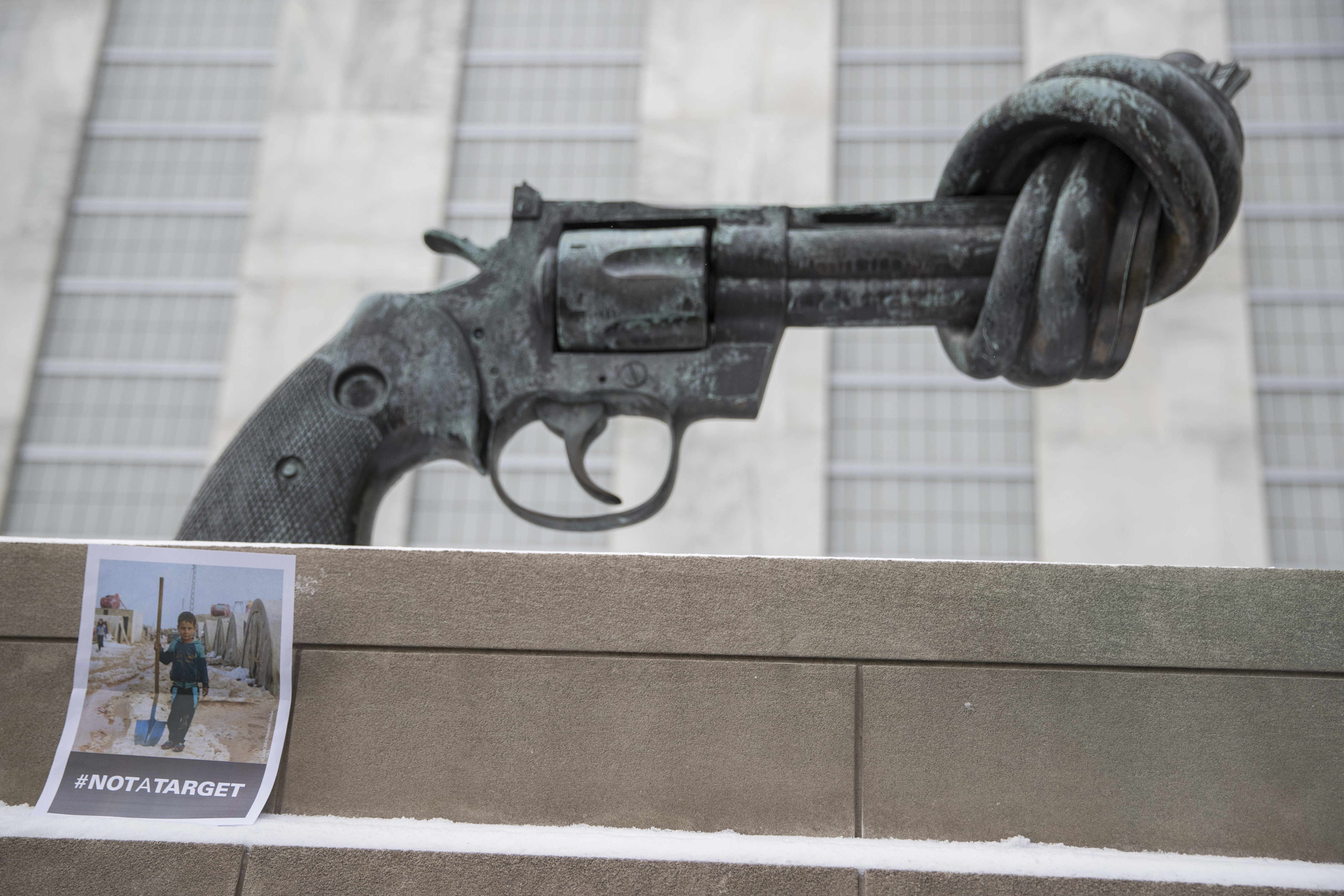 "A photo of a Syrian child is placed next to ""Non-Violence"" by Swedish artist Carl Fredrik Reutersward, after a moment of silence was observed, March 15, 2017 at United Nations headquarters in New York to mark the 6th anniversary of the Syrian conflic..."