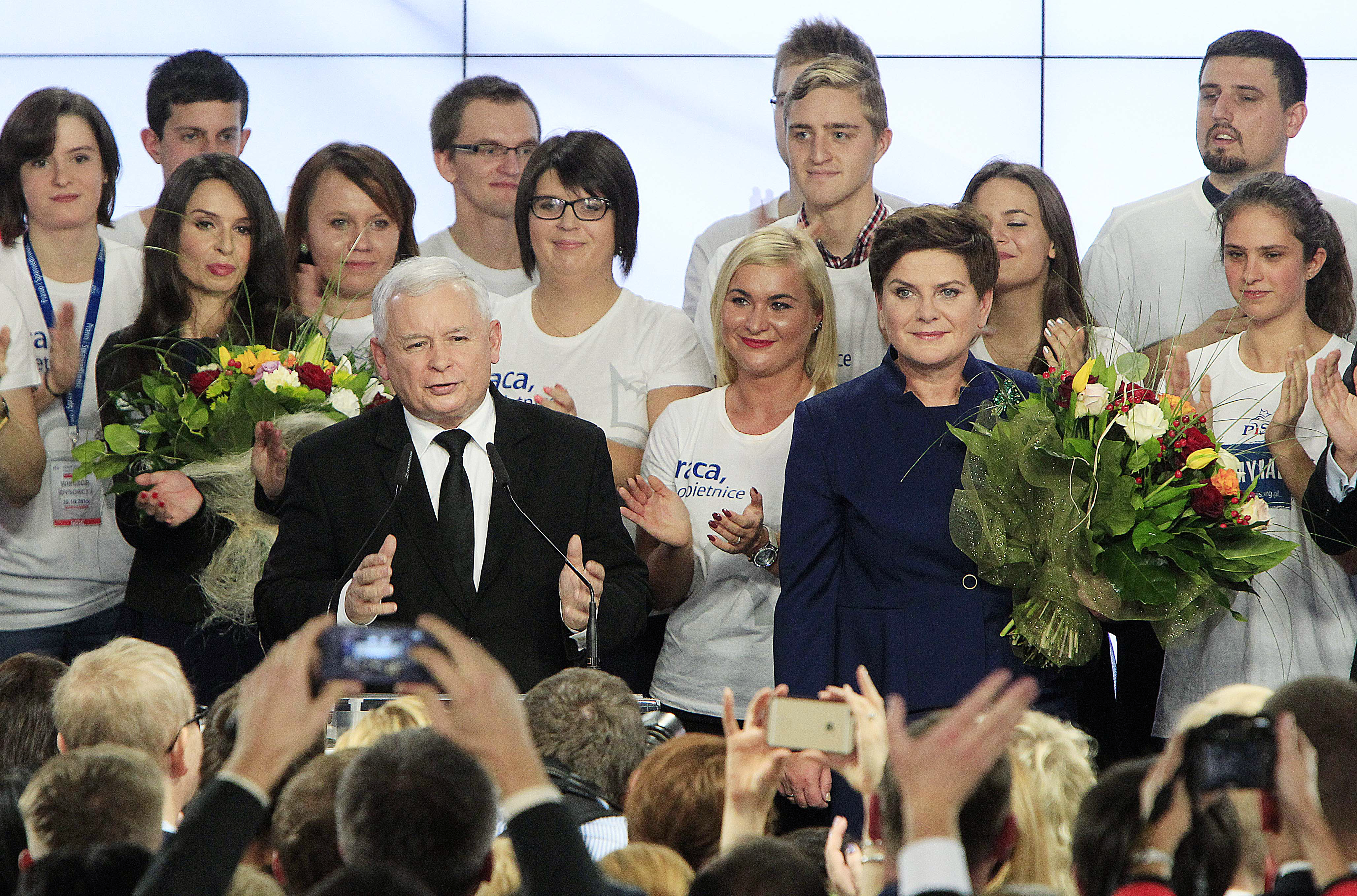 Conservative Law and Justice leader Jaroslaw Kaczynski, center left, along with Justice candidate for Prime Minister Beata Szydlo, center right, delivers a speech at the party's headquarters in Warsaw, Poland, Oct. 25, 2015.
